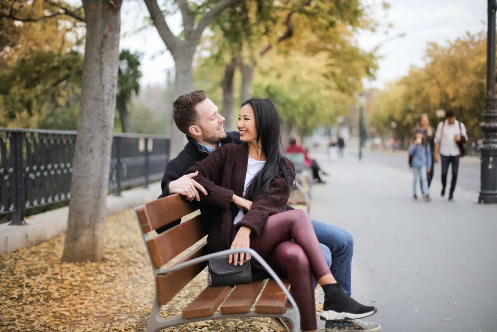 homme et femme souriant alors qu'il était assis sur un banc