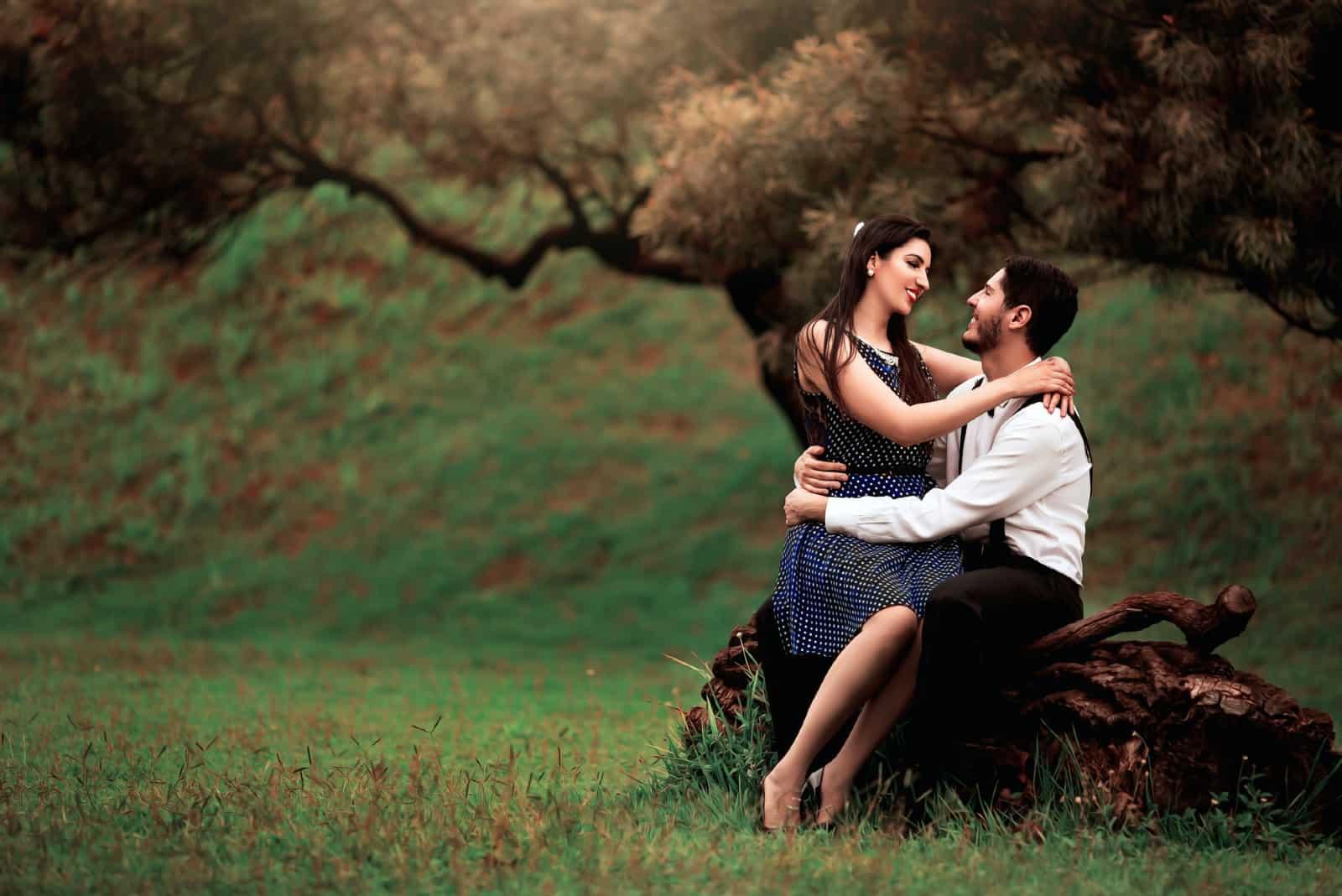 homme et femme étreindre quoique séance sur tronc arbre