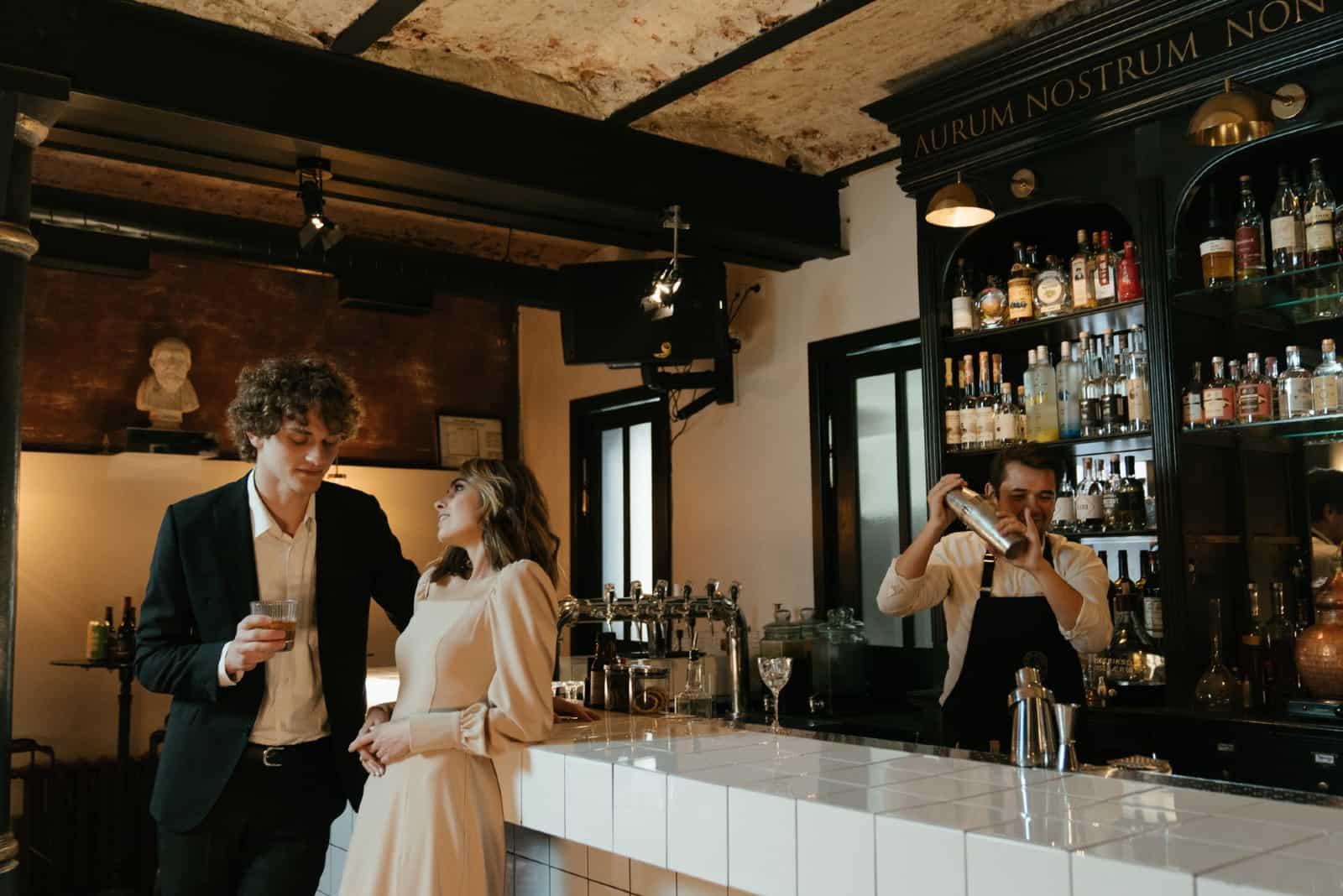 couple buvant des boissons debout dans un bar