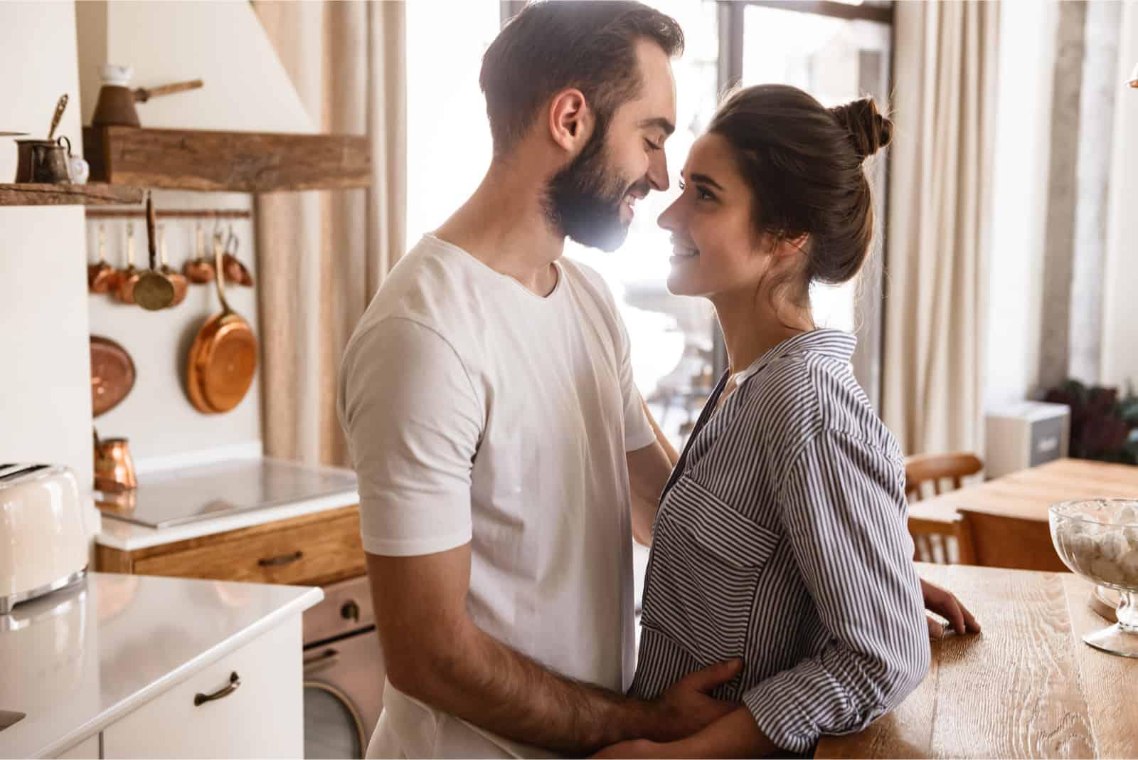 homme et femme établissant un contact visuel tout en se tenant à l'intérieur