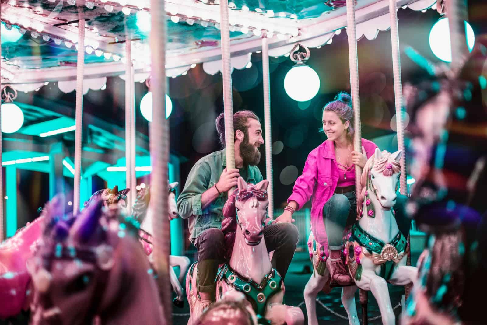 homme et femme tenant par la main tout en équitation carrousel