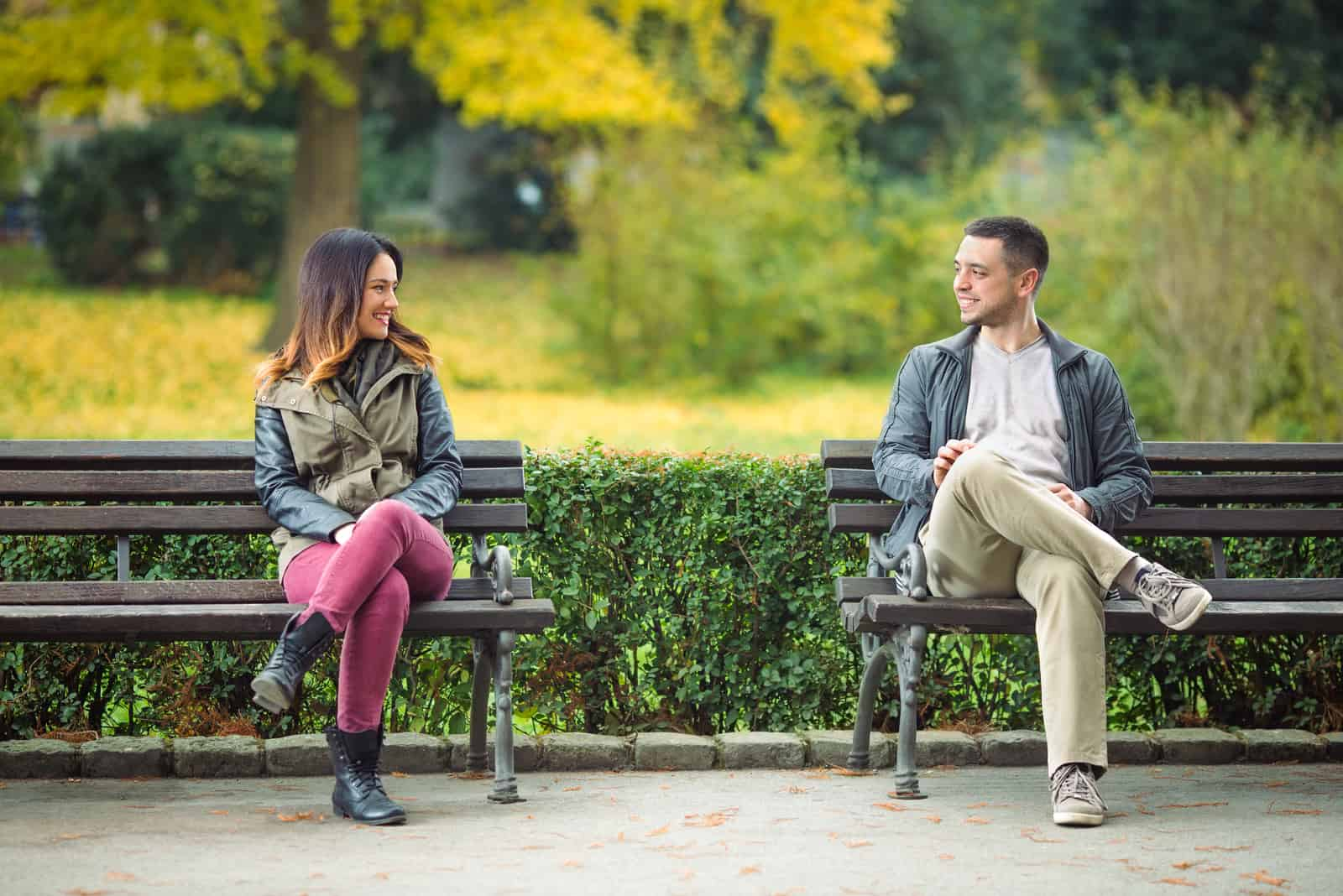 Un homme et une femme se contactent en s'asseyant sur un banc.