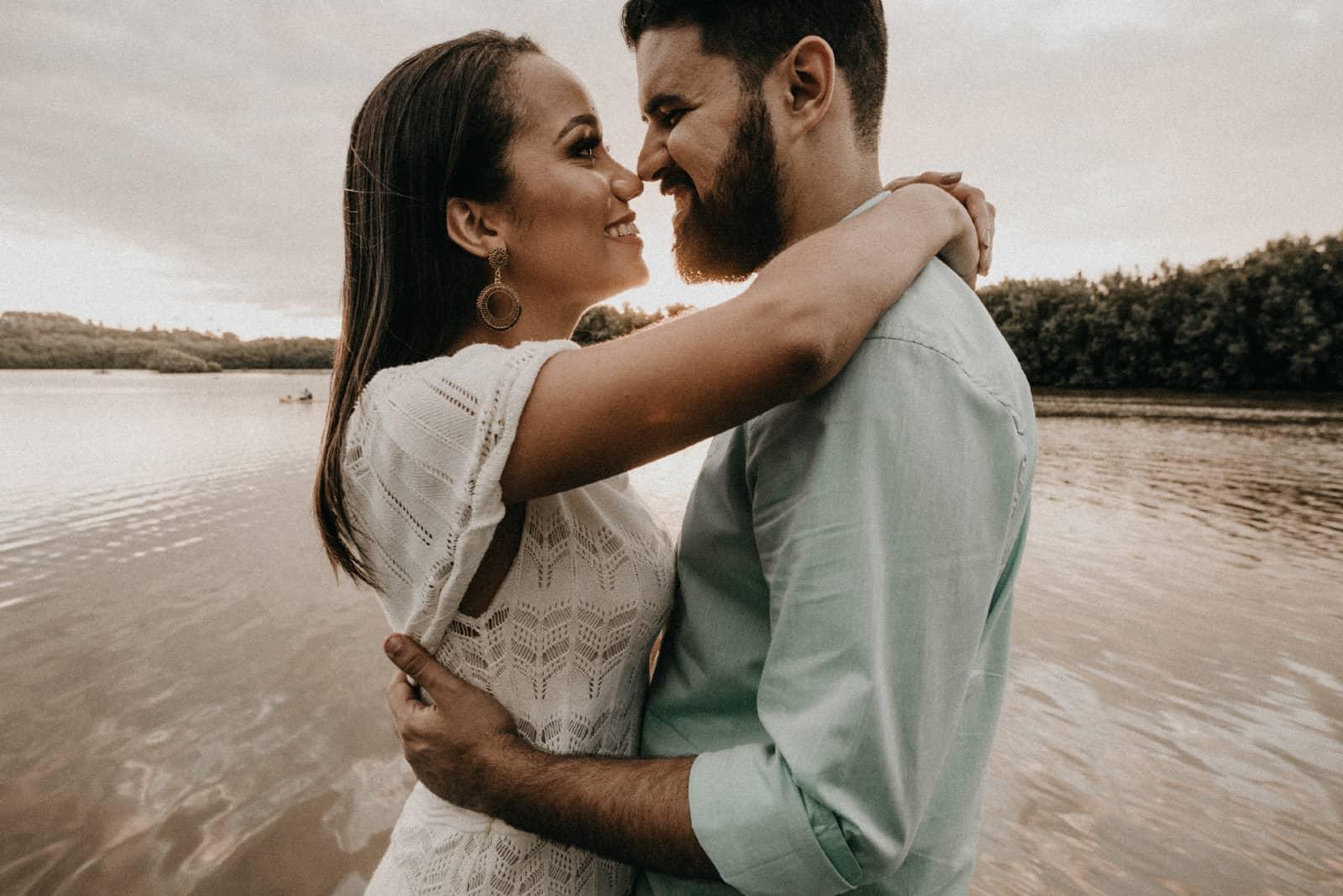 homme et femme étreindre quoique debout près  lac