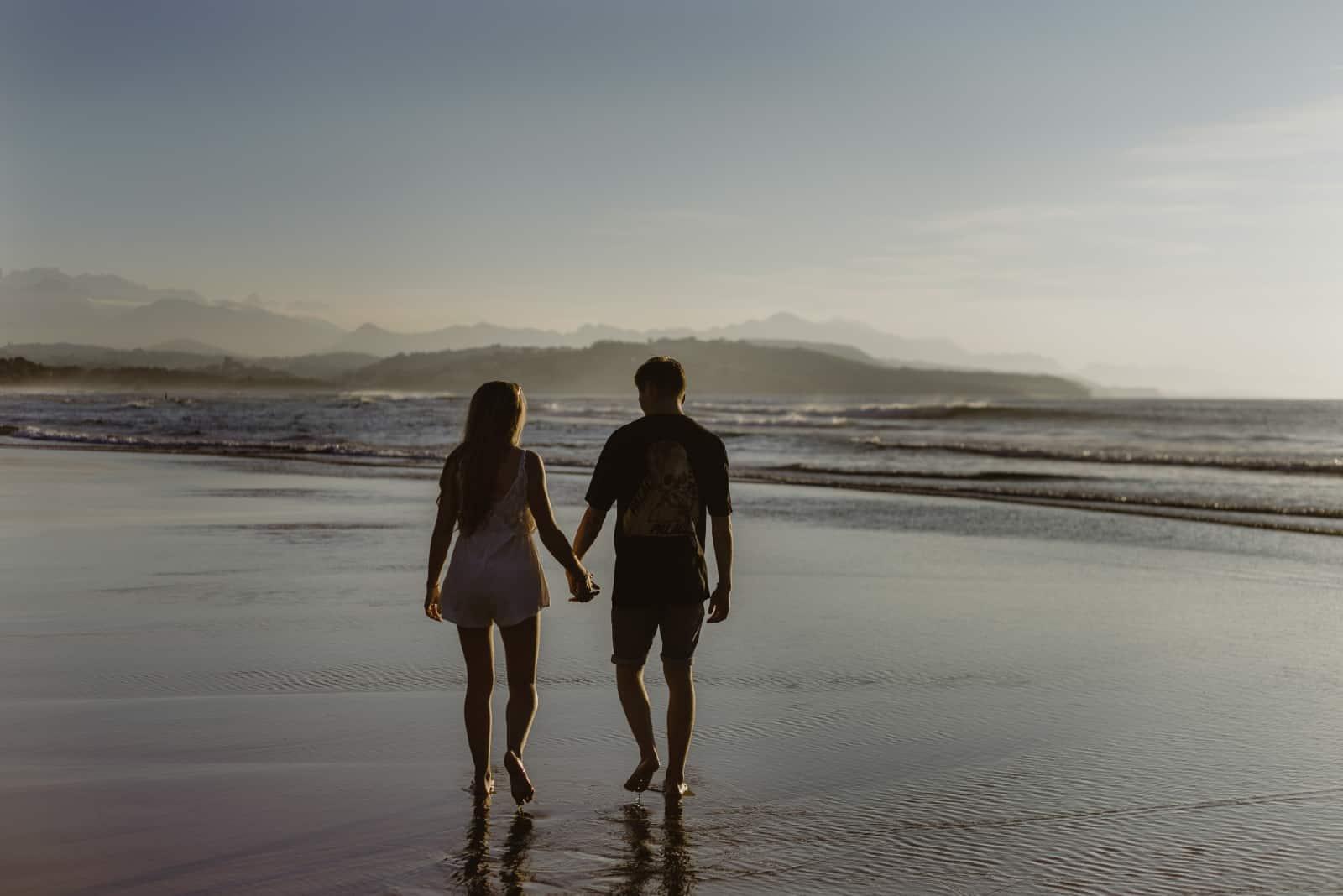 homme et femme main dans la main en marchant sur la plage