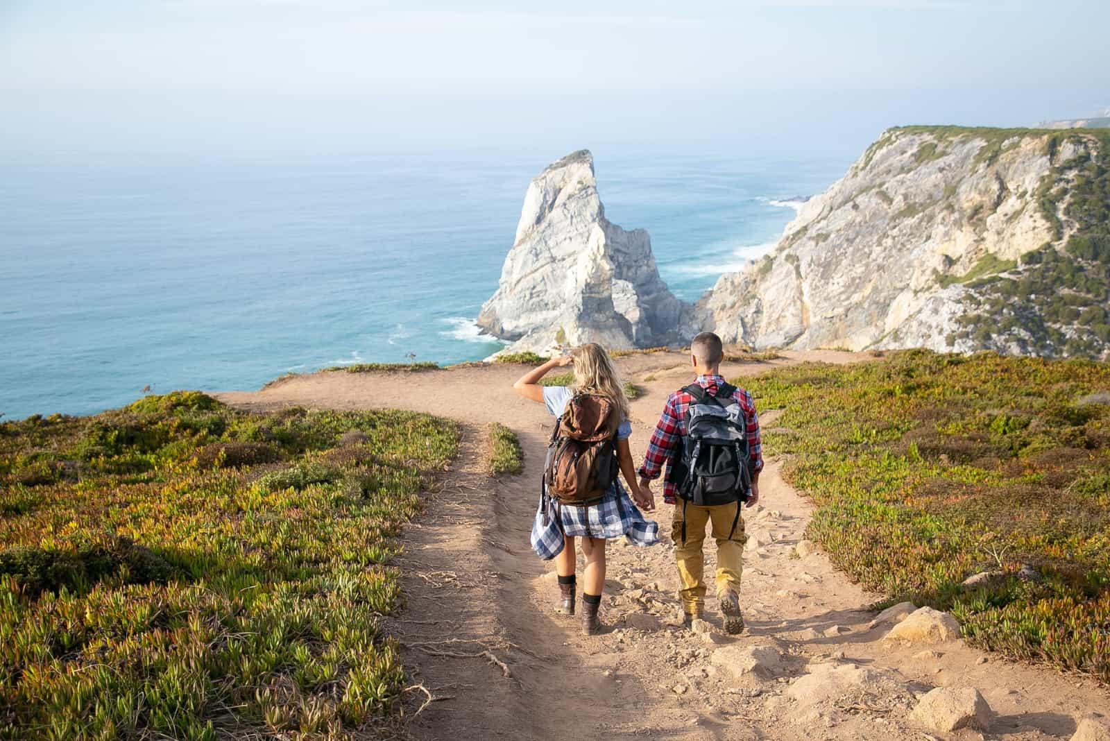 homme et femme avec des sacs à dos marchant