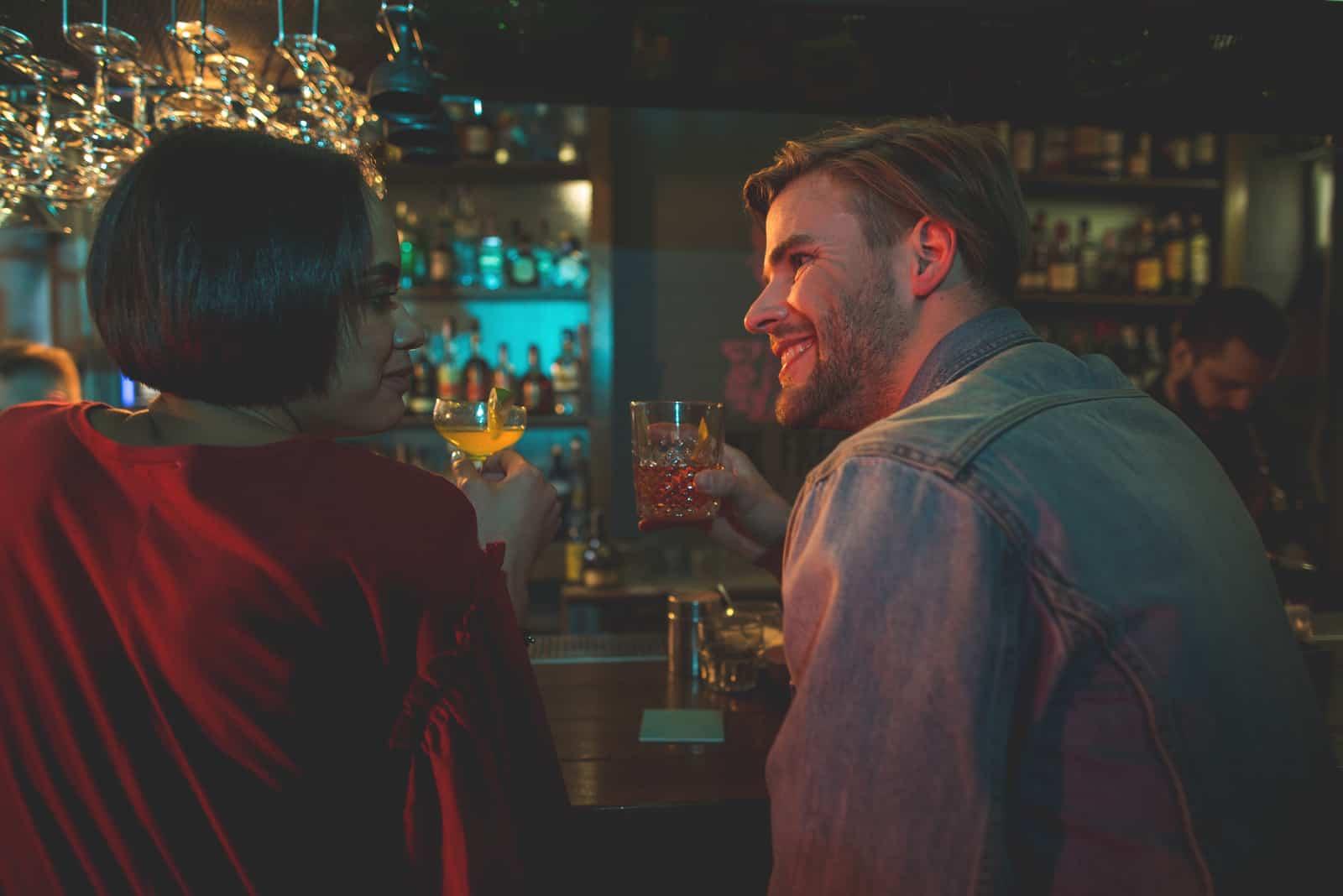 homme et femme prenant un verre dans un bar