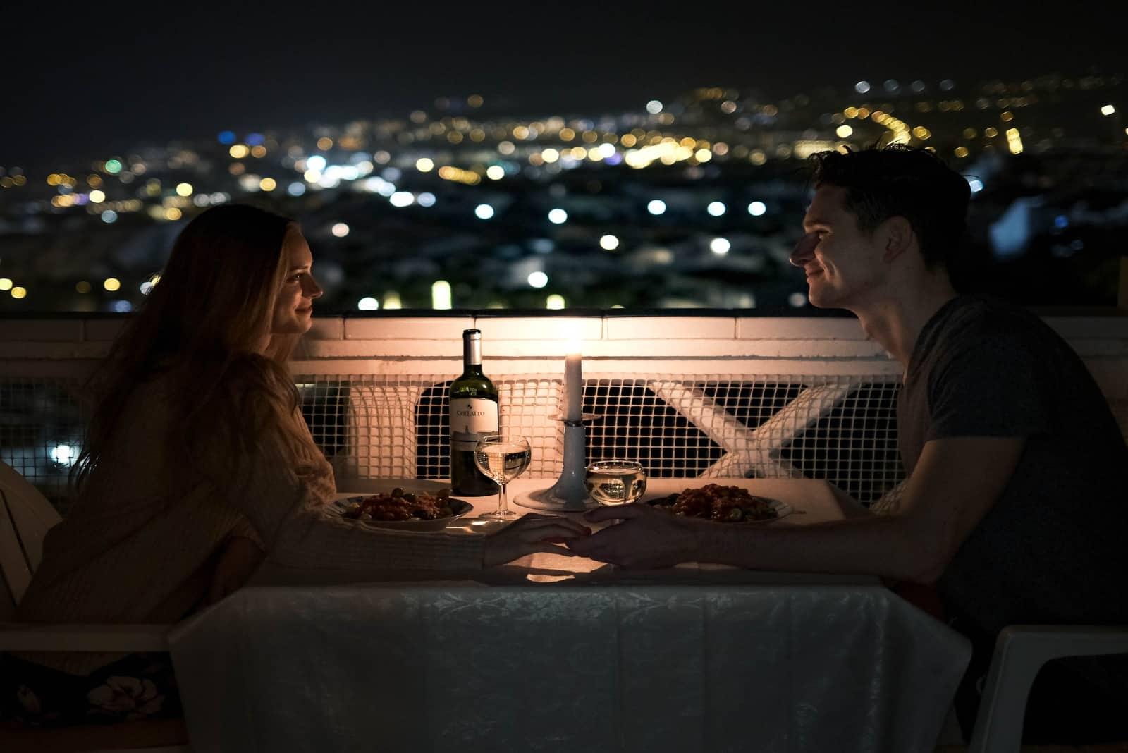 homme et femme se tenant la main à table