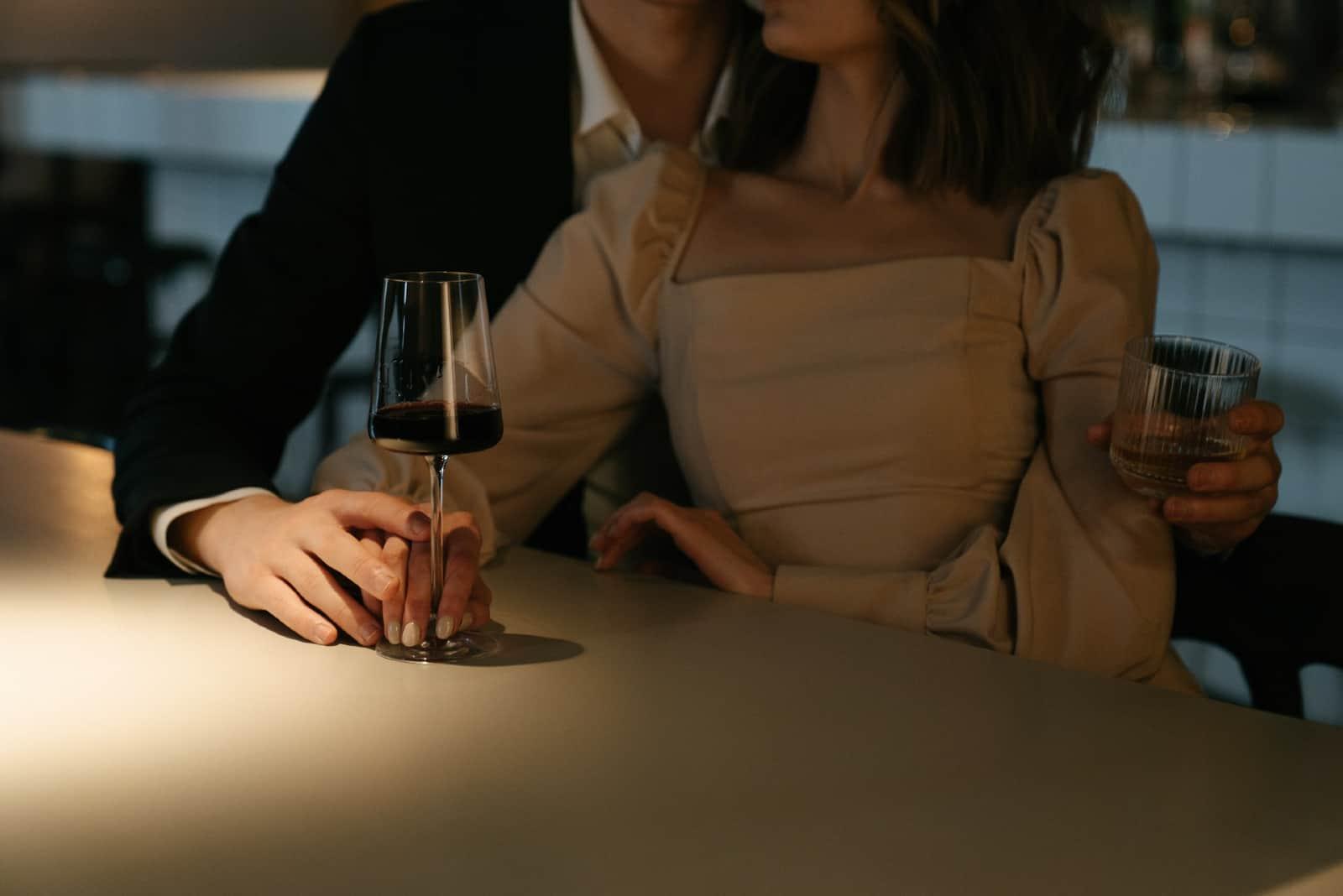 homme et femme tenant des boissons alors qu'il était assis à table