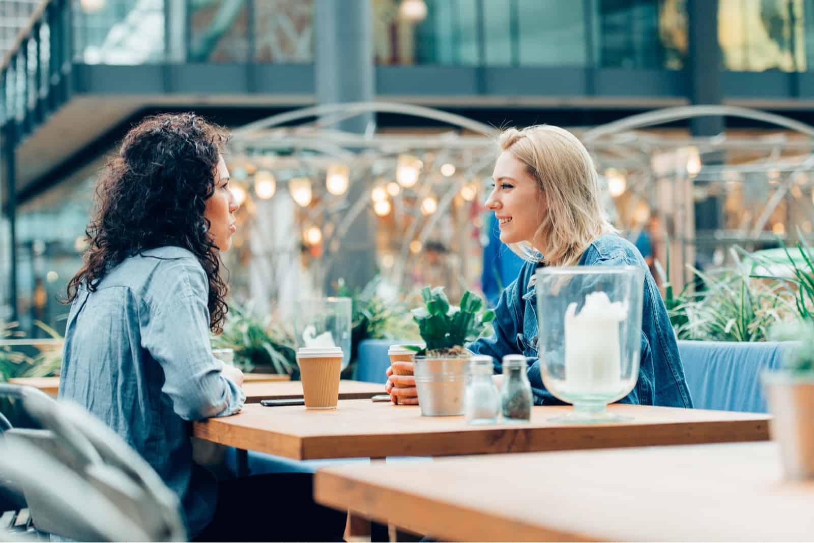deux amis sont assis à une table et parlent