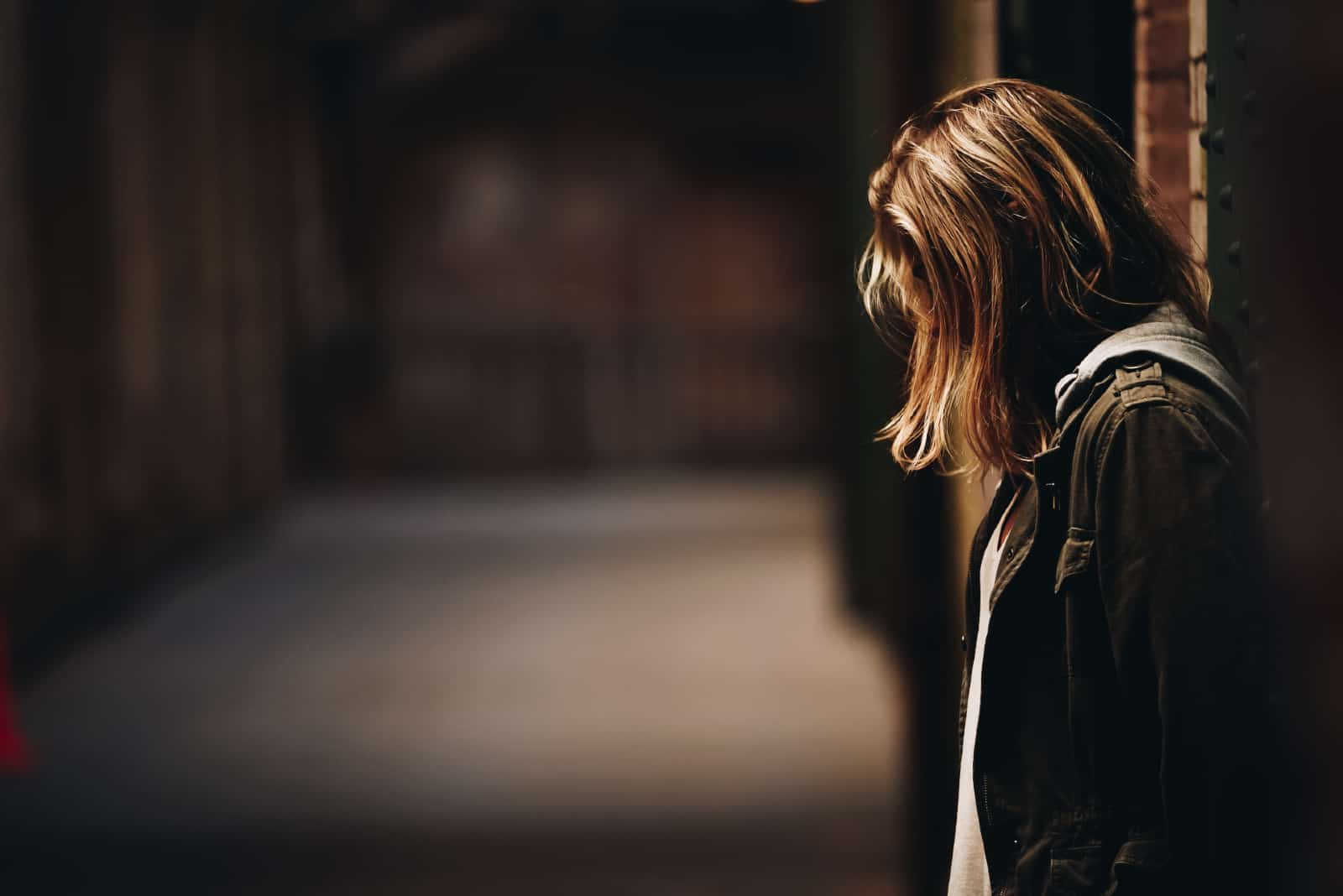 femme triste en veste verte appuyée sur un mur