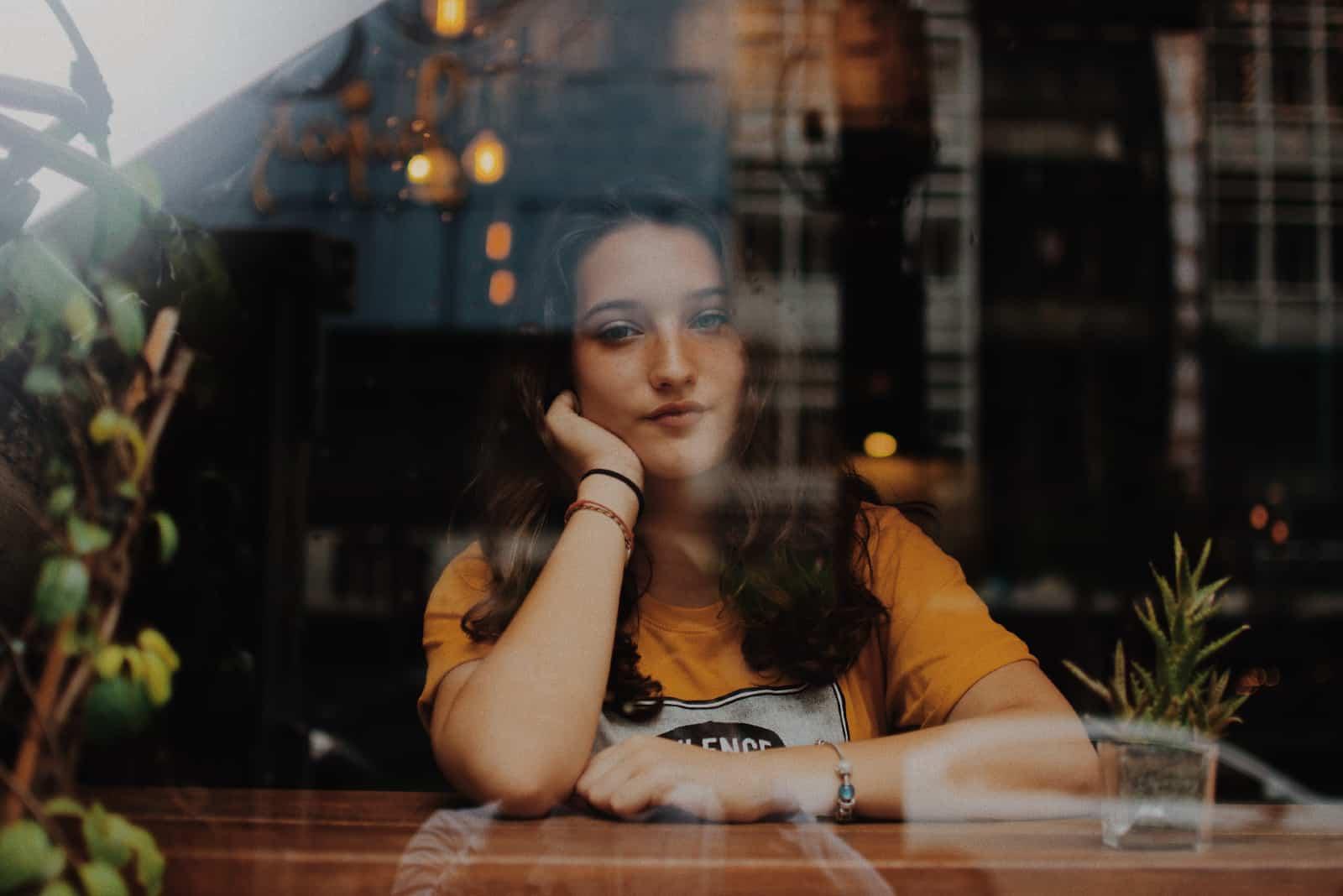 femme triste en t-shirt jaune appuyée sur une table