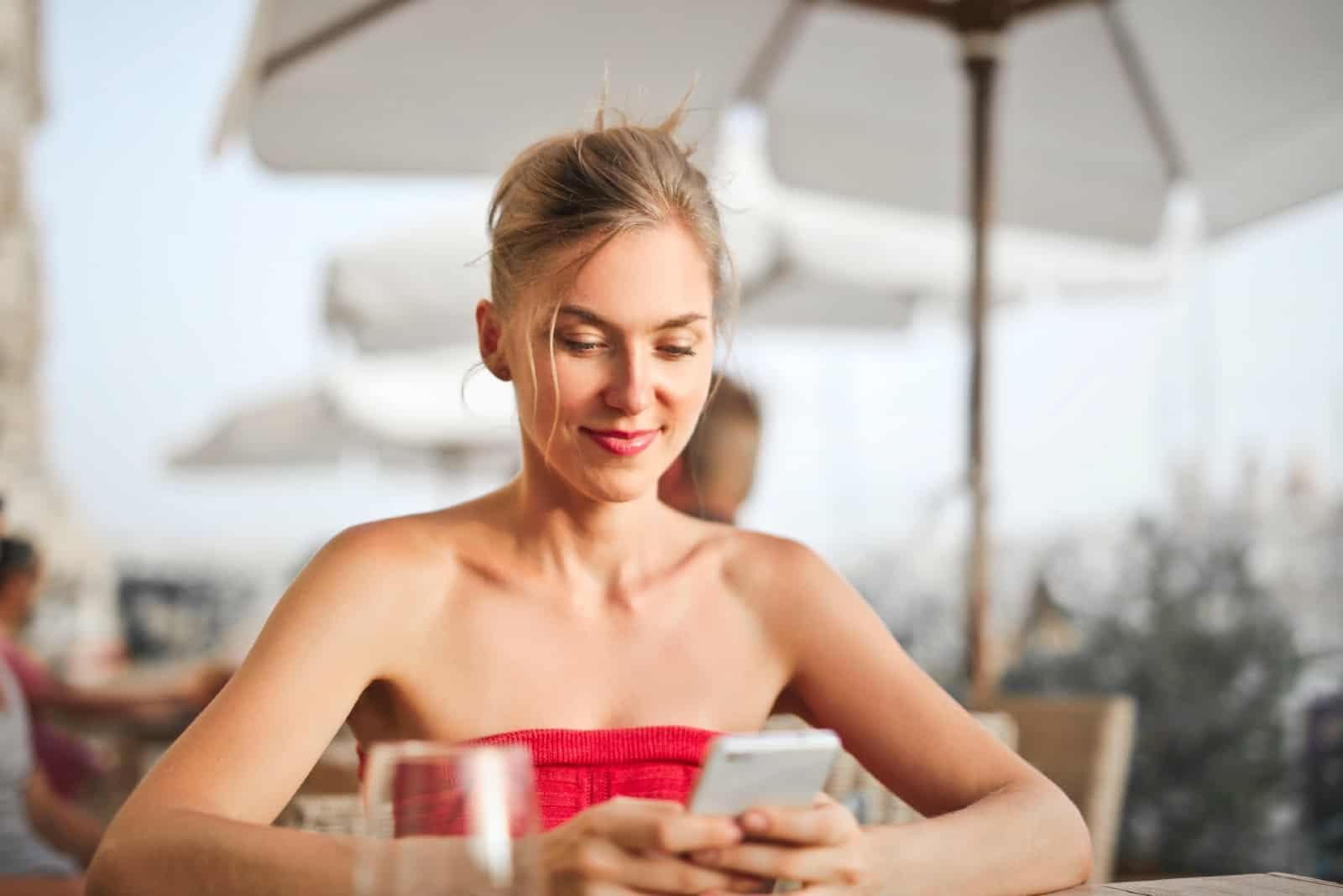 femme heureuse séance table regarder smartphone