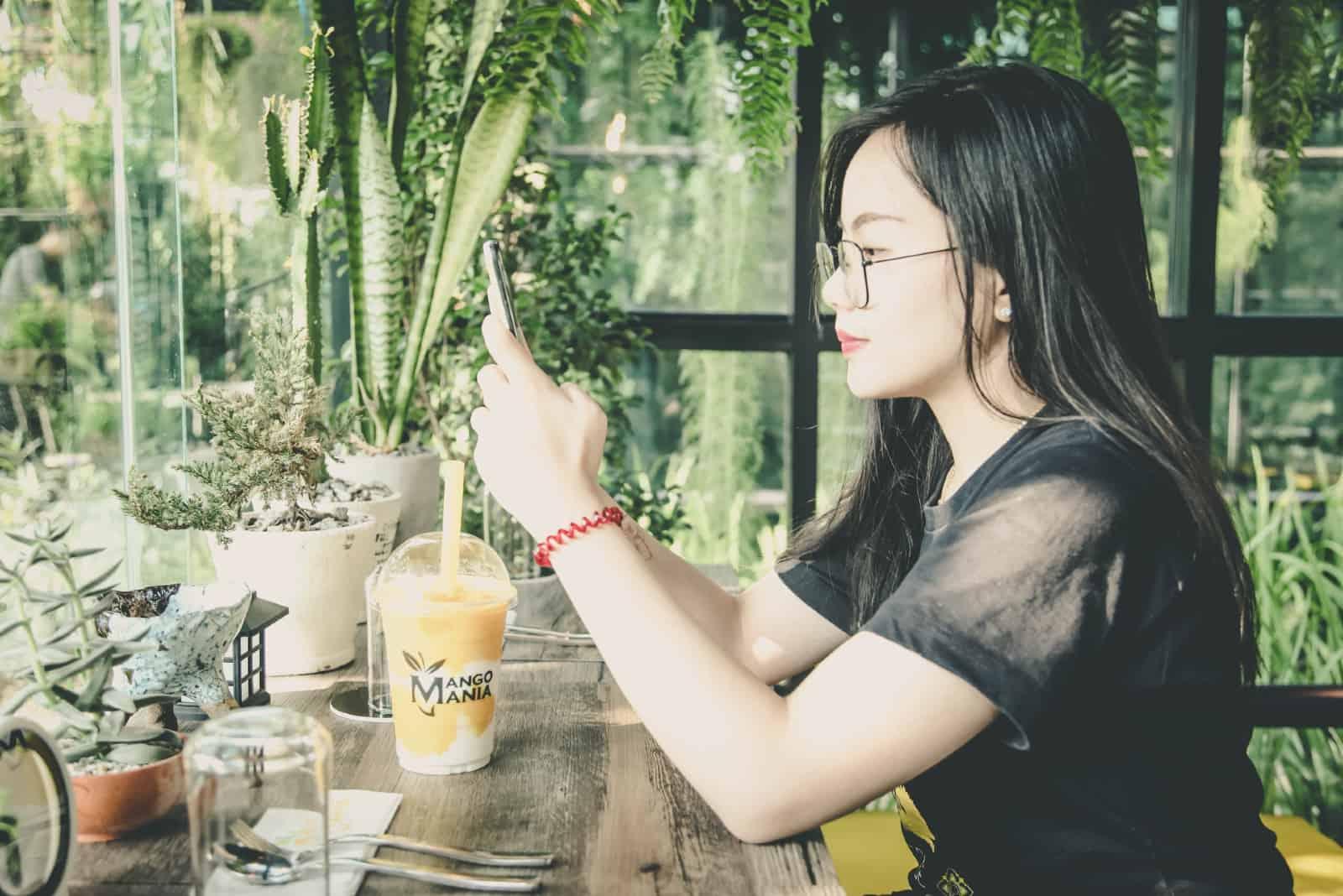 femme assise à une table utilisant un smartphone