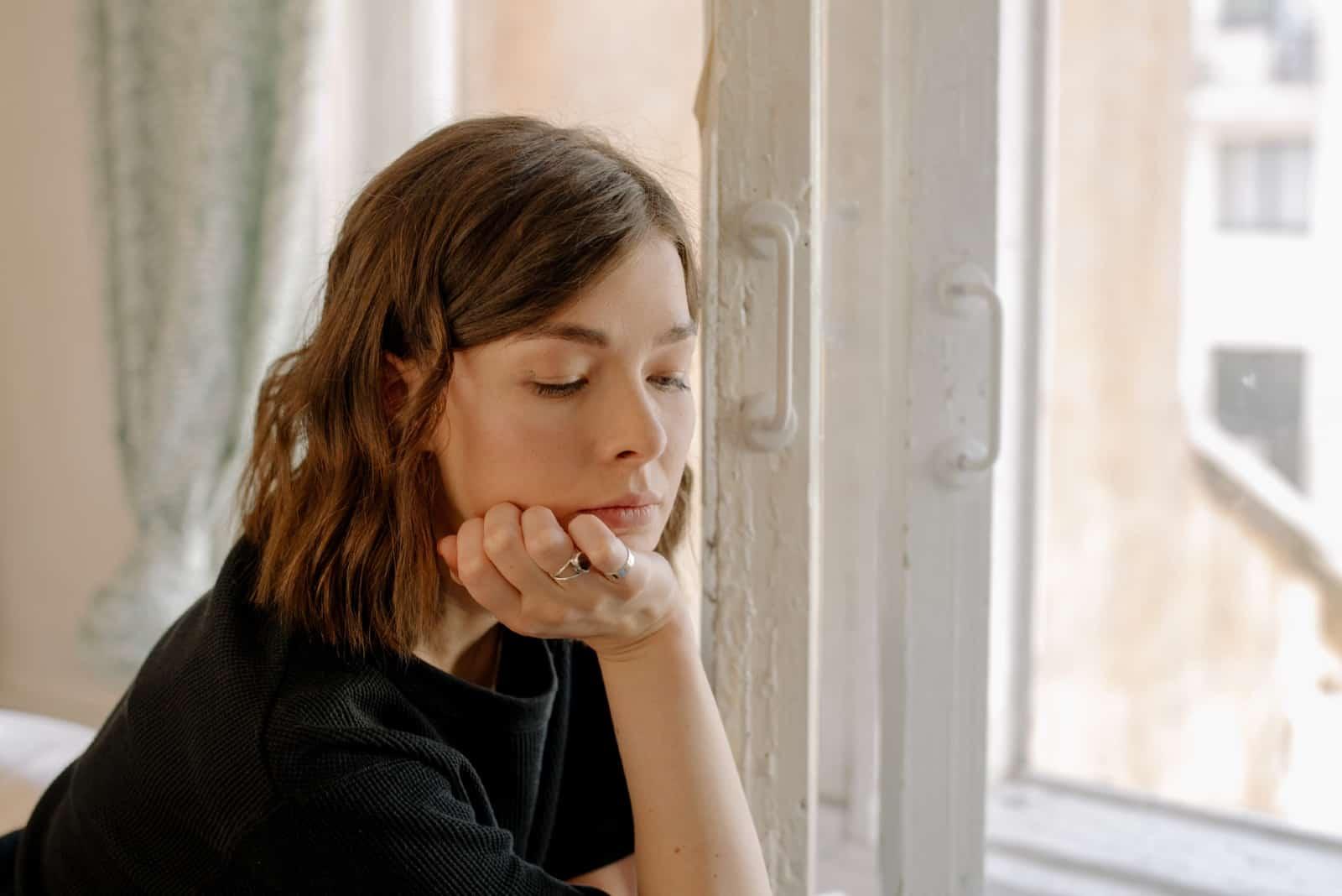 femme triste en t-shirt noir assis près de la fenêtre