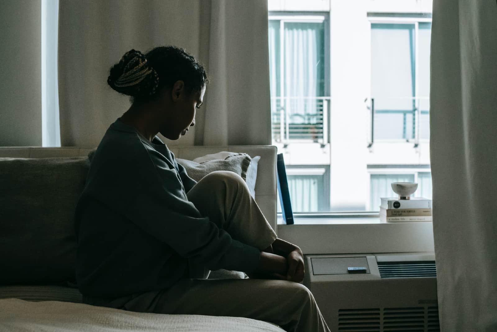 femme triste en sweat-shirt bleu assis sur le lit