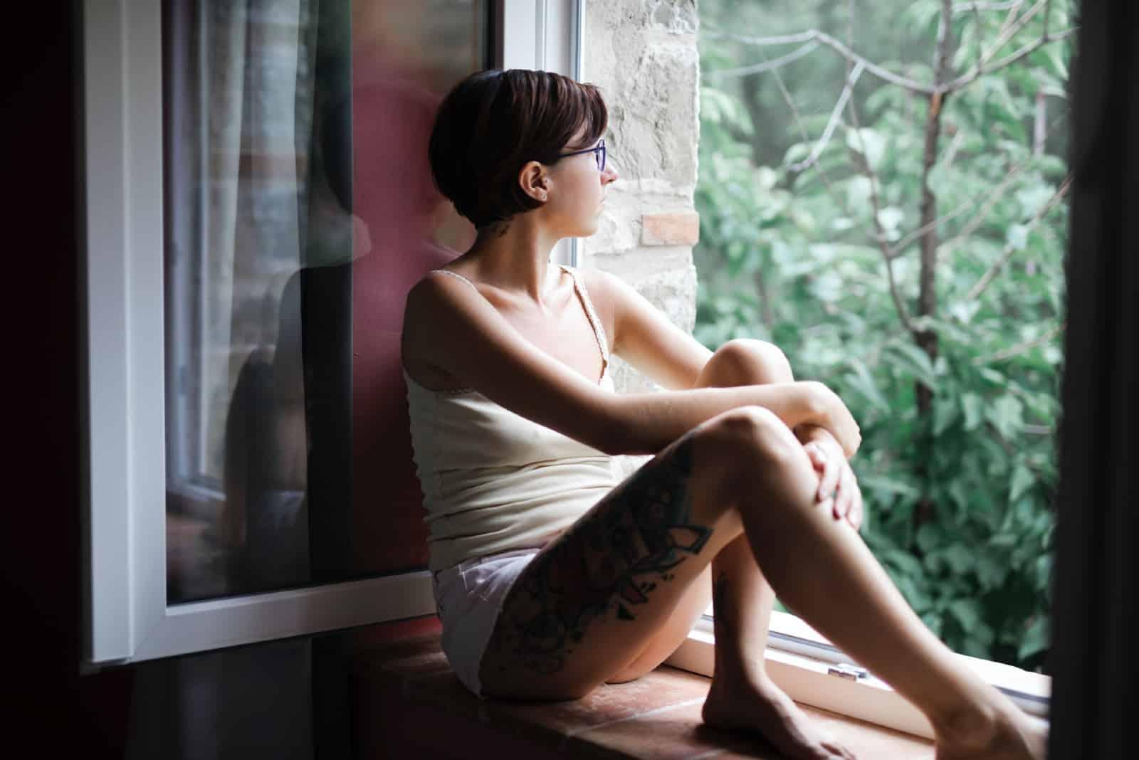 Femme assise sur le rebord de la fenêtre à l'extérieur