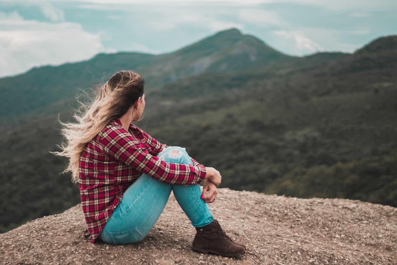femme assise sur le sol en regardant la montagne