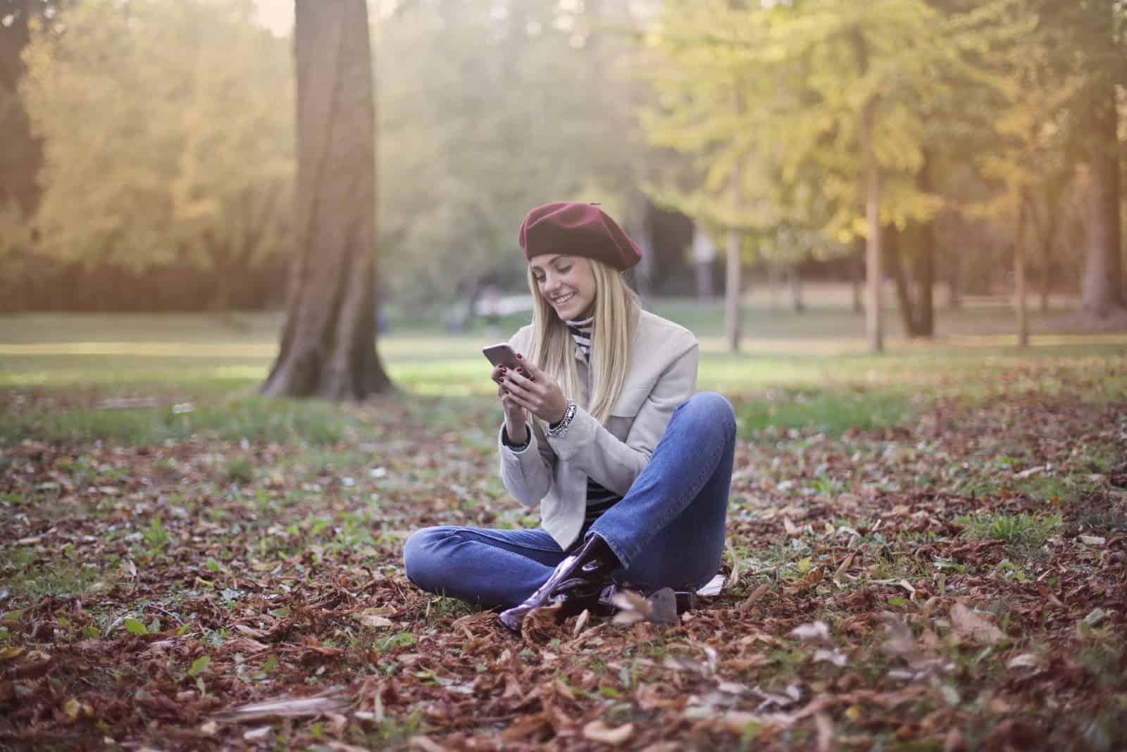 femme heureuse séance sur feuilles regarder smartphone