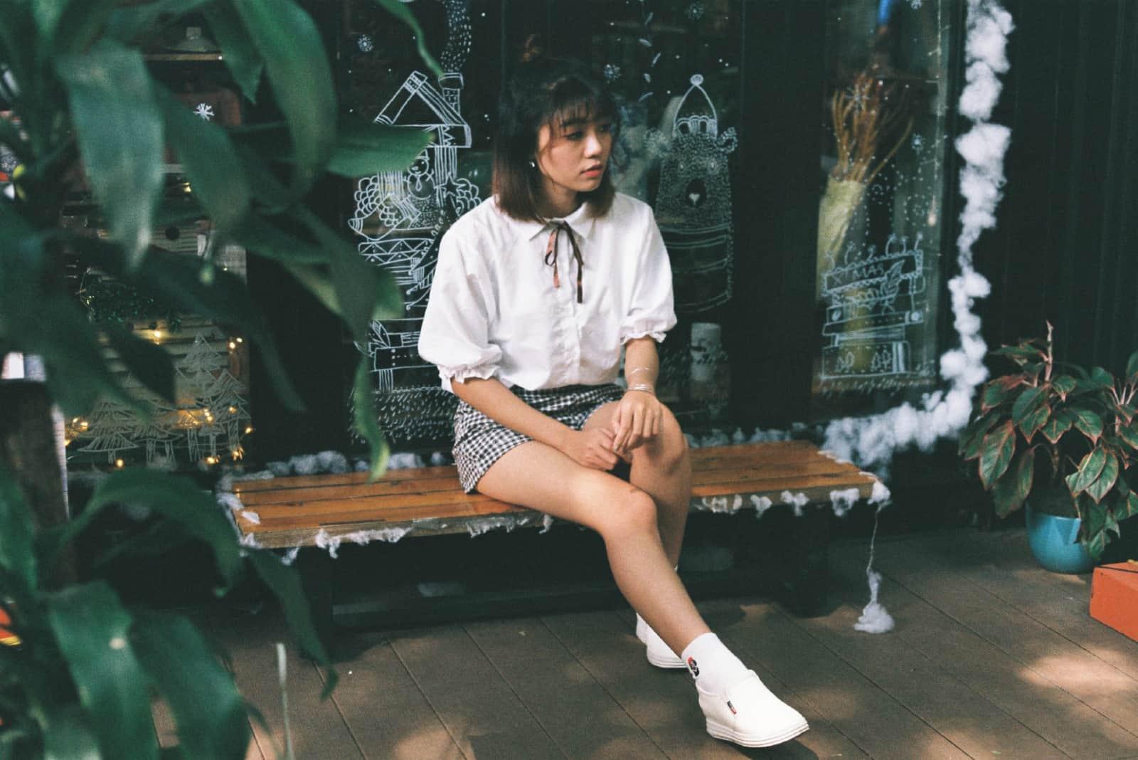 Femme pensive en chemisier blanc assis sur un banc
