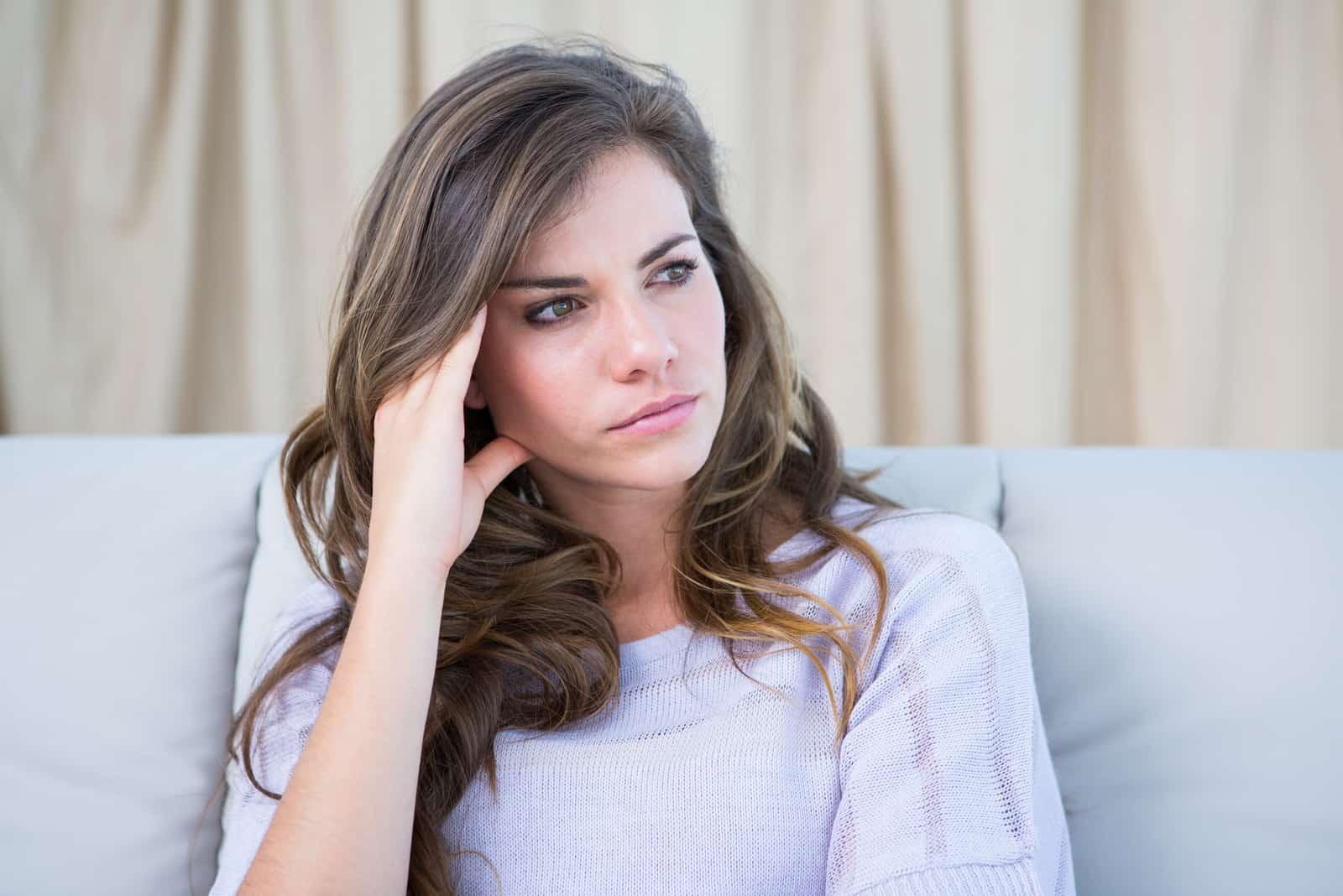 Femme pensive en pull gris assis sur un canapé
