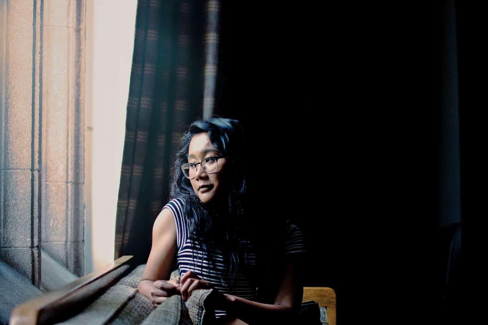 Femme pensive en haut rayé assis sur un canapé
