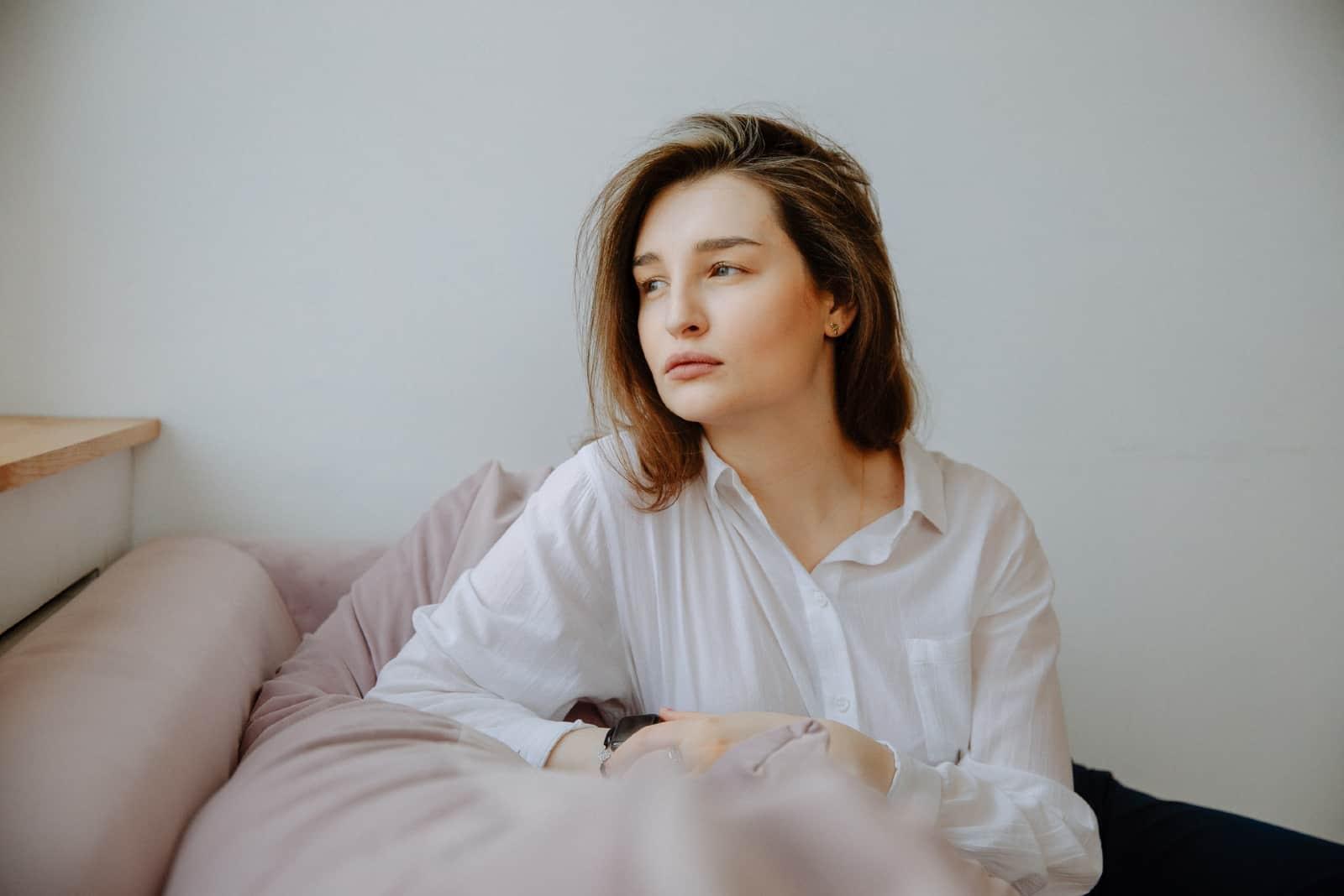 Femme pensive en chemise blanche assise sur un canapé