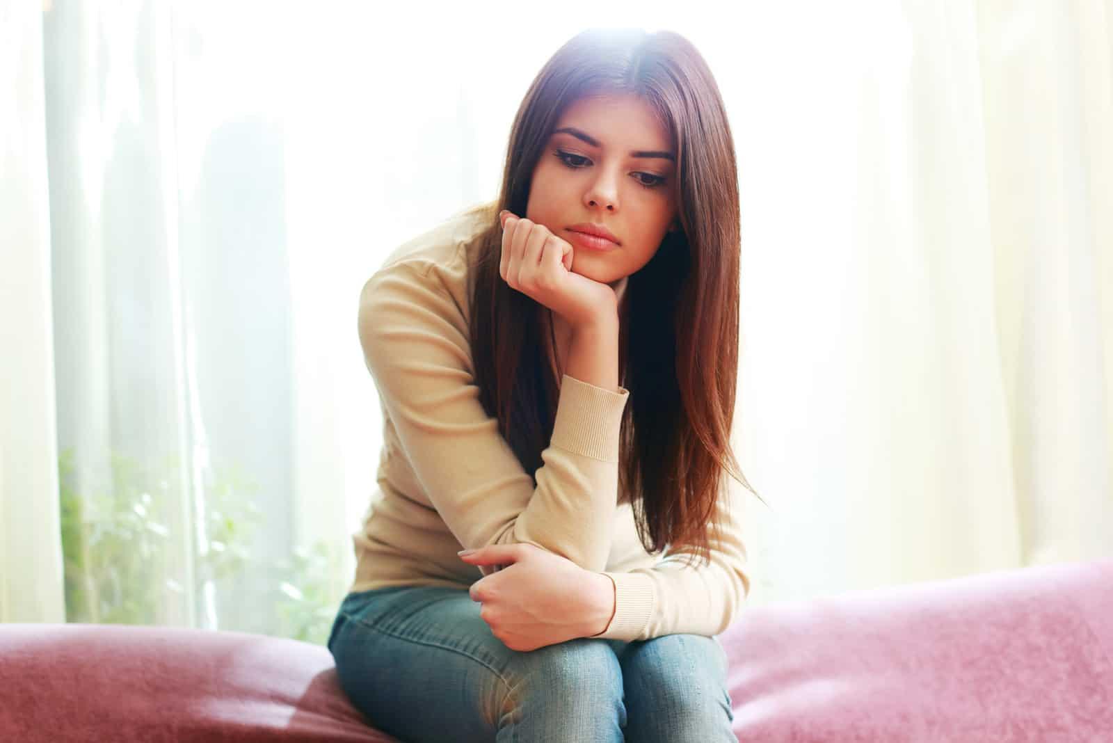 femme triste assise sur un canapé près d'un rideau blanc