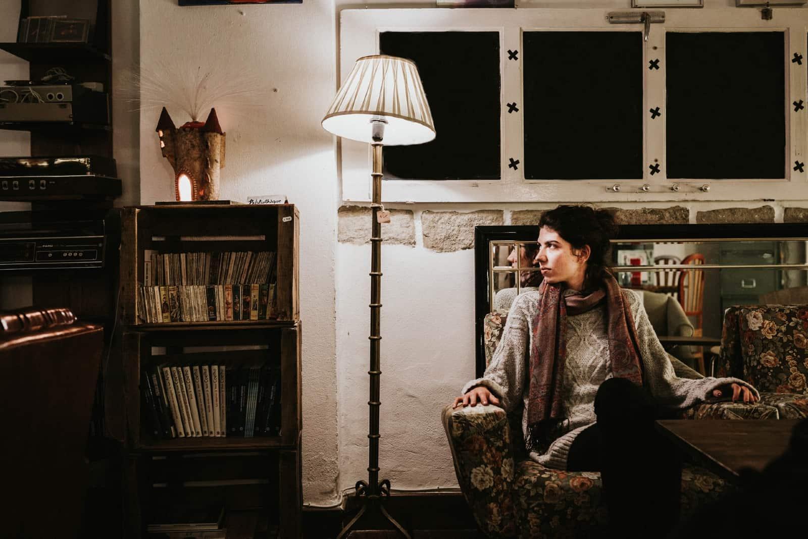 femme pensive avec foulard assis sur un fauteuil