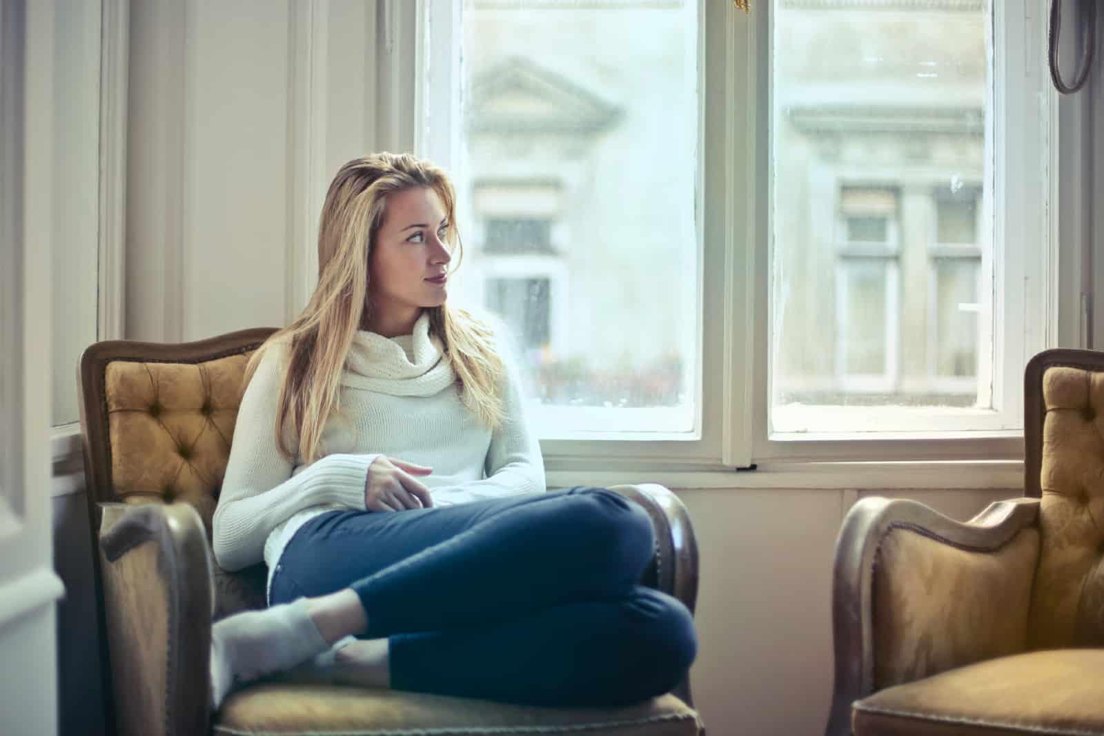 Femme blonde en pull blanc assis sur un fauteuil