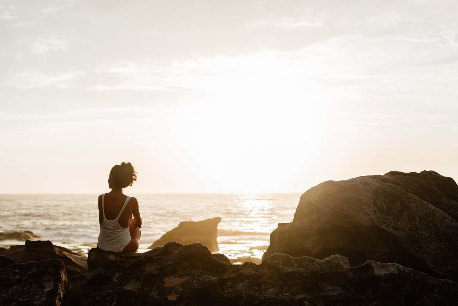 femme en maillot de bain blanc assis sur un rocher