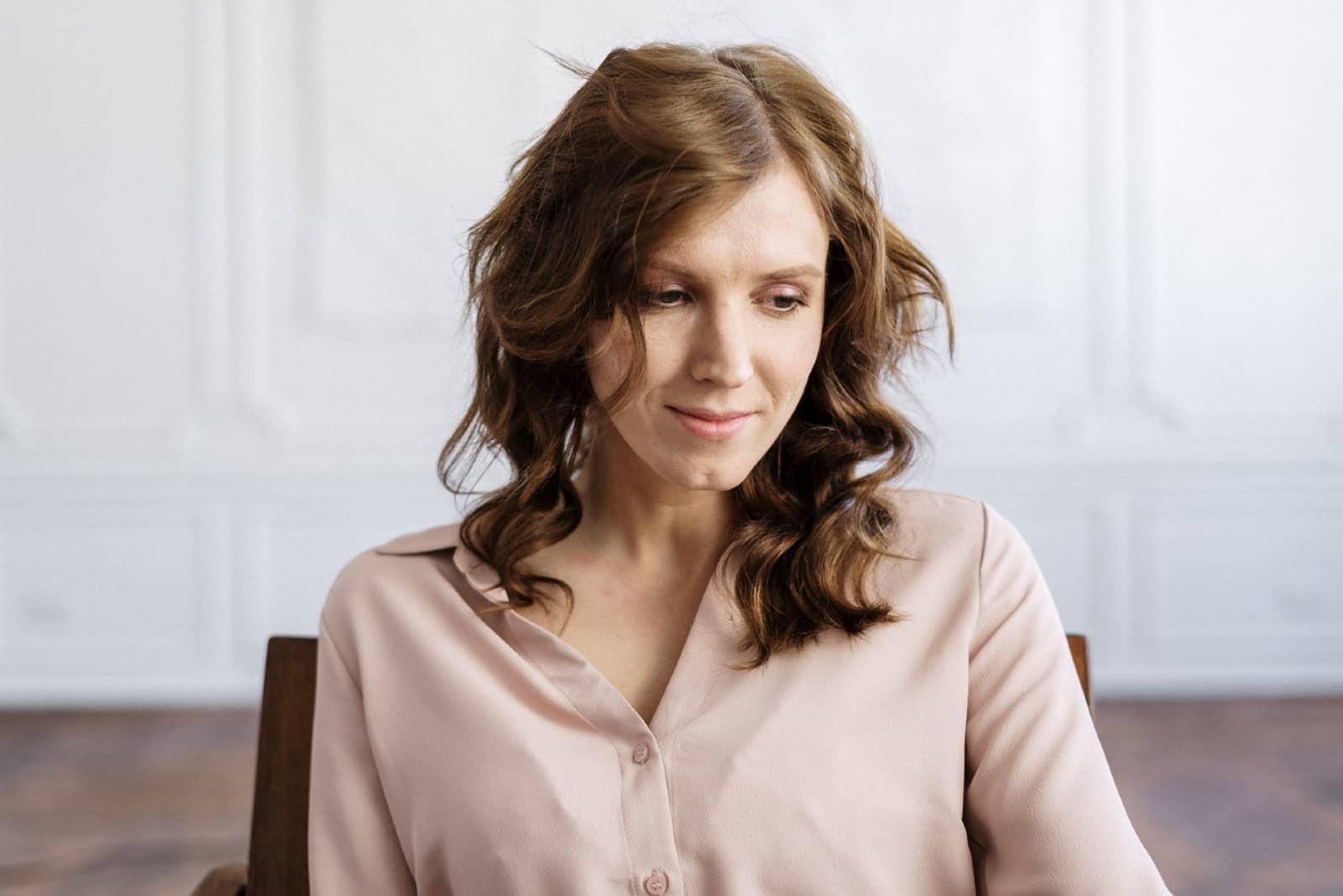 Femme triste en chemise boutonnée blanche assise sur une chaise