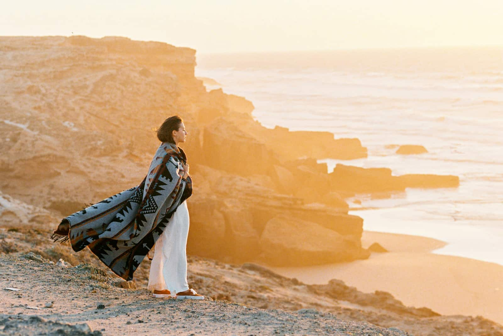 femme avec couverture volante debout sur le bord de la falaise