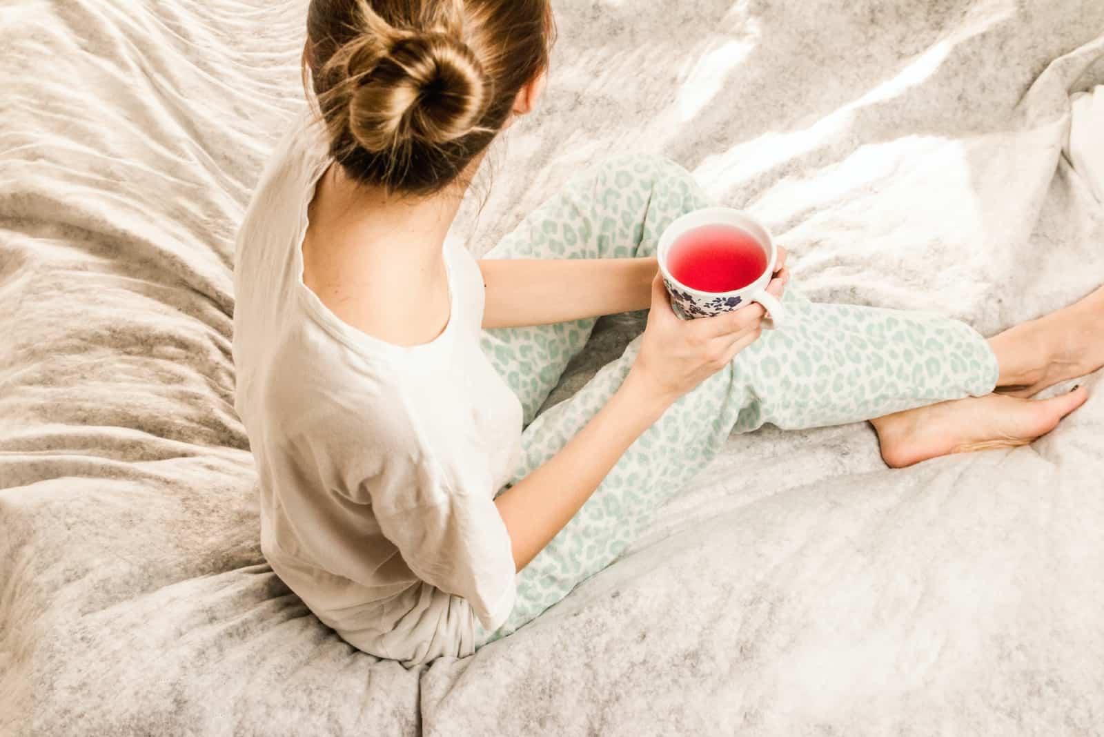 femme buvant du thé assise sur un lit