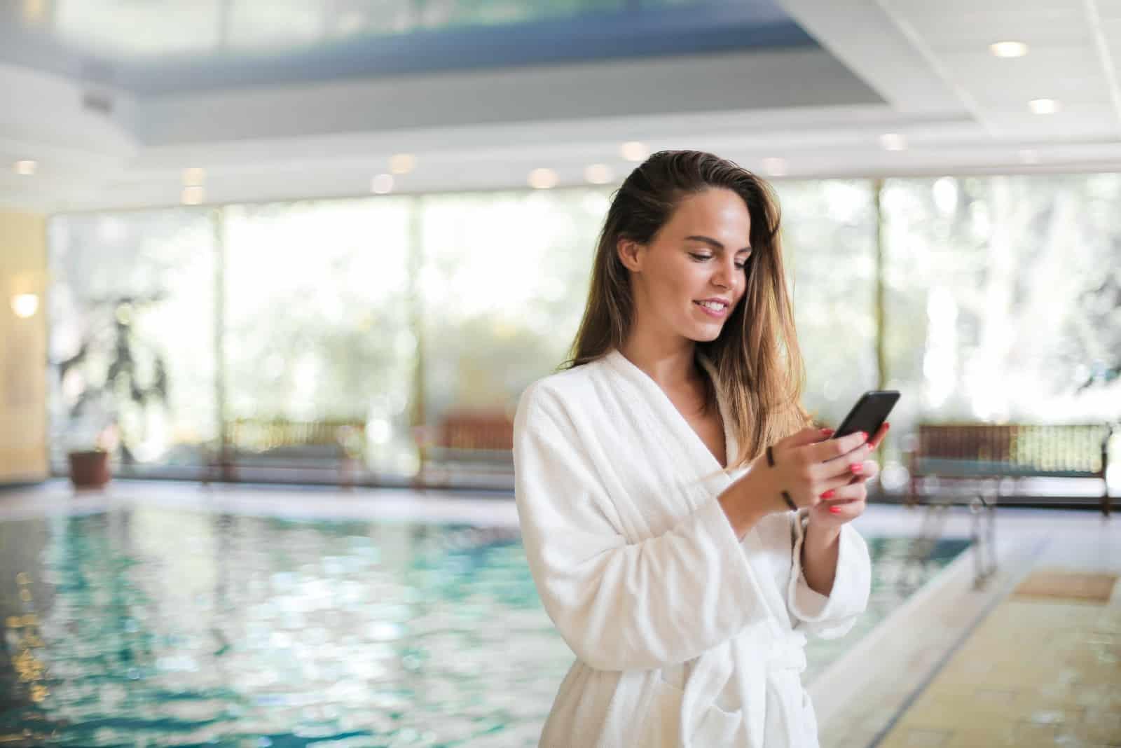 femme en robe blanche à l'aide de smartphone