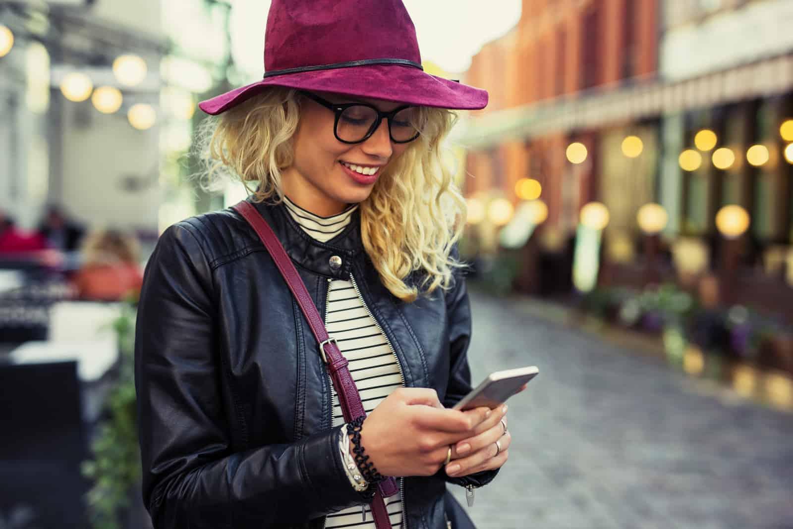 Femme blonde à l'aide de smartphone en se tenant debout dans la rue