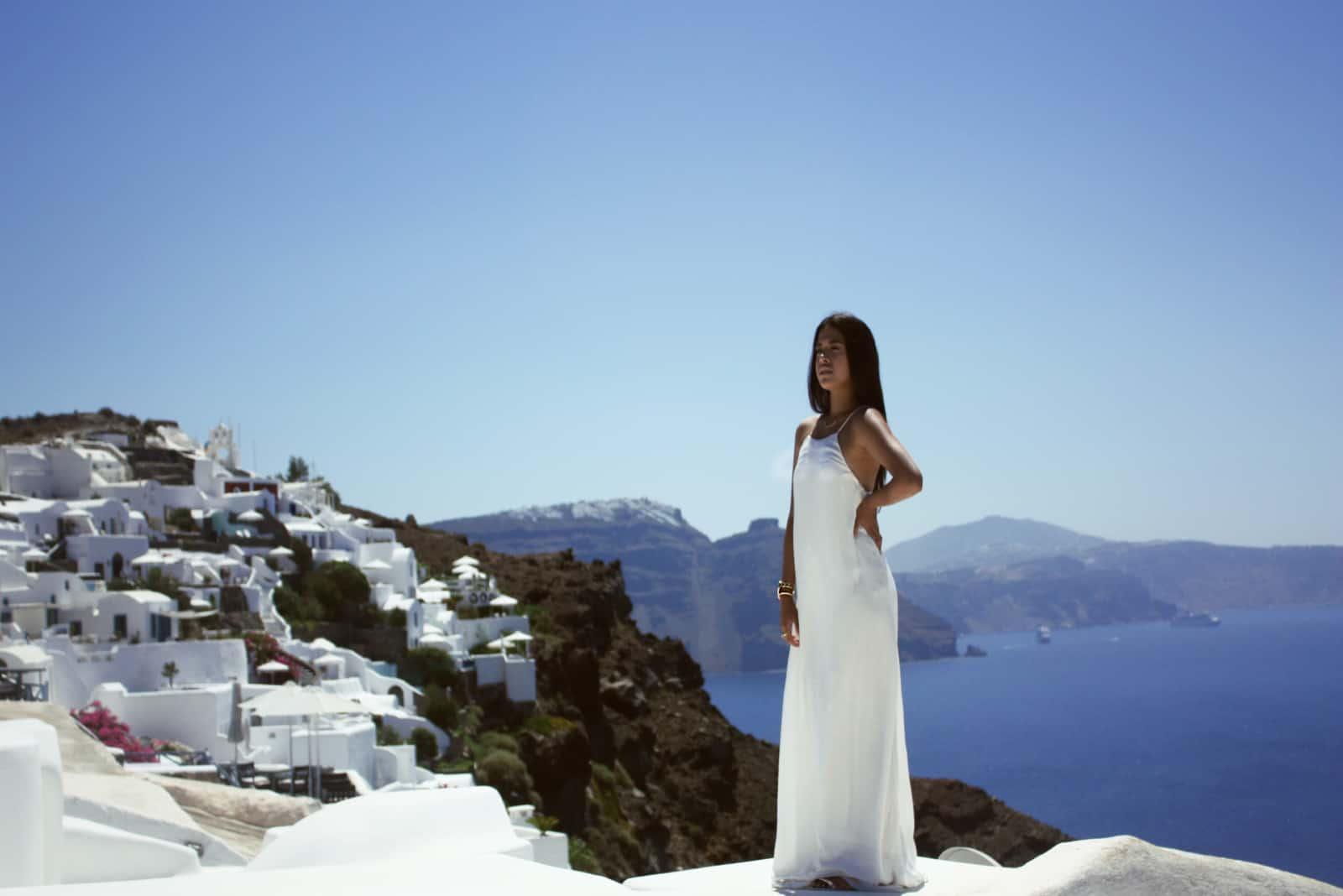 femme en robe blanche devant un bâtiment au bord de la mer