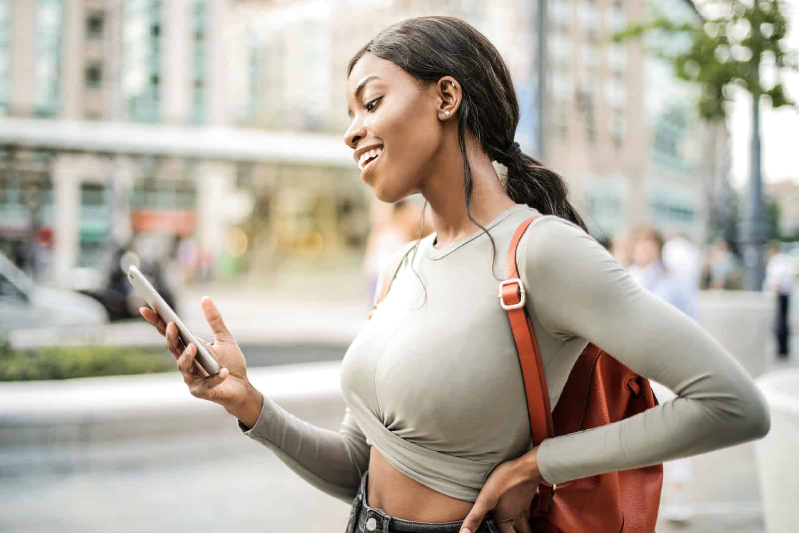 femme heureuse debout extérieur regarder smartphone