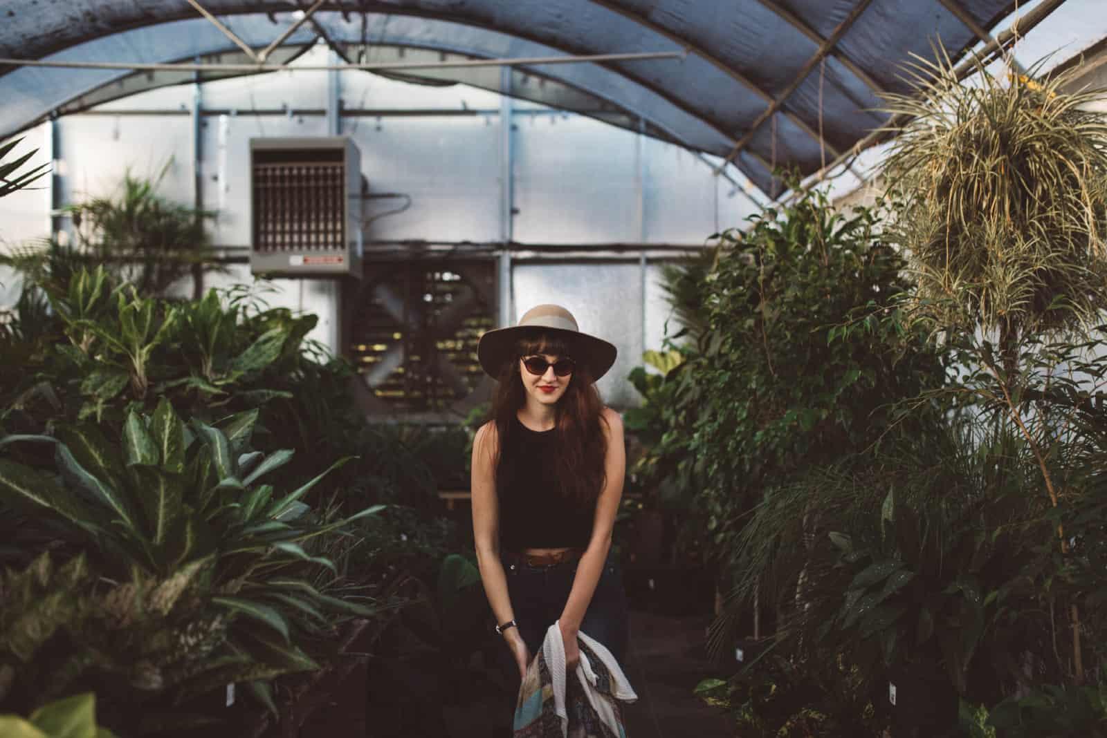 femme heureuse avec des lunettes de soleil debout entre les plantes