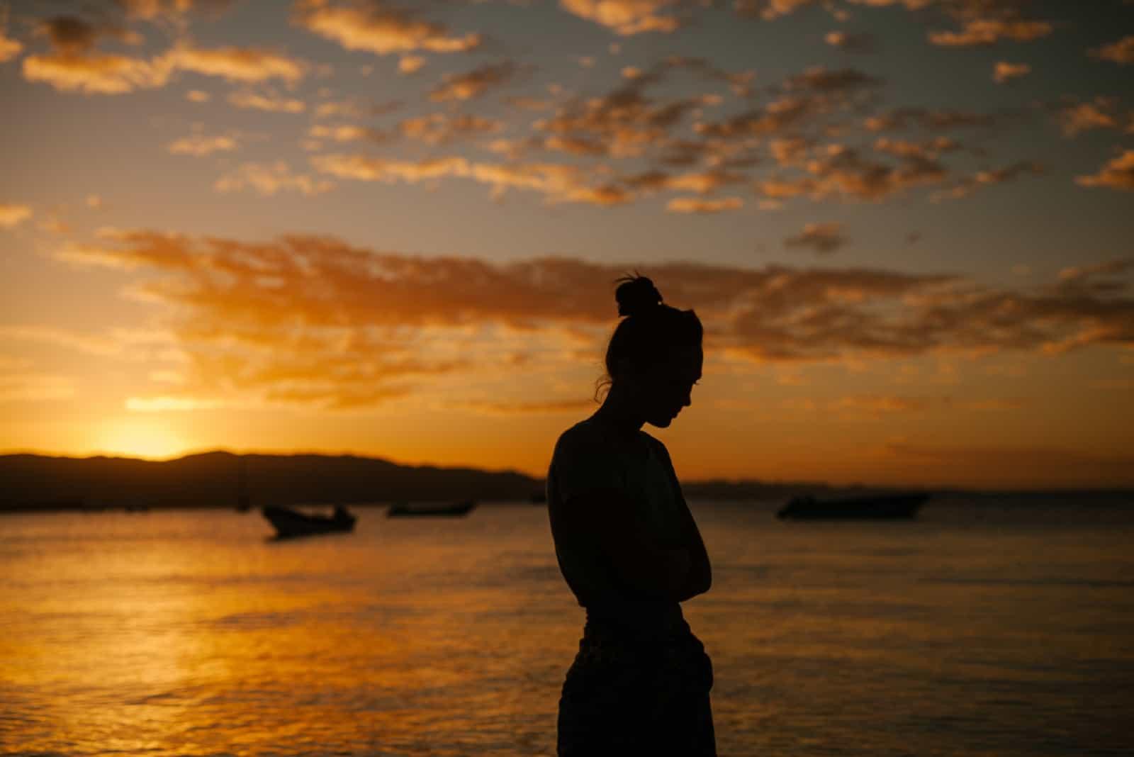 triste, femme, debout, près, mer, pendant, coucher soleil