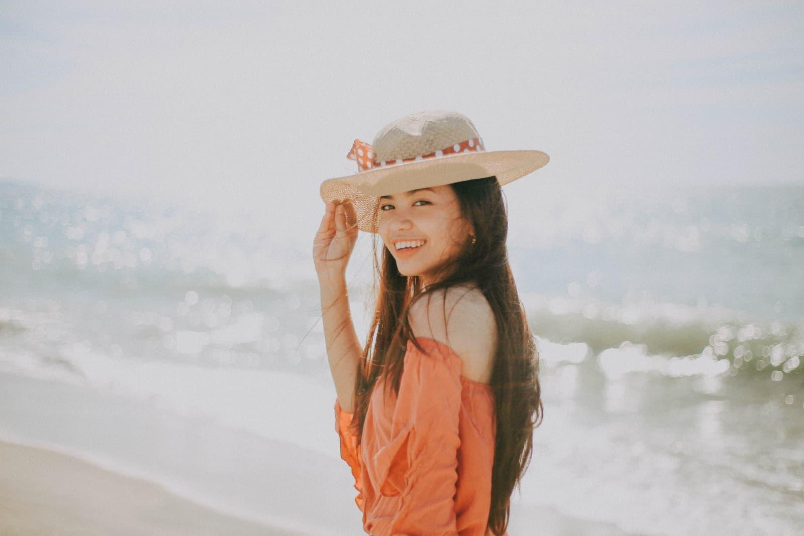 femme heureuse avec chapeau debout près de la mer