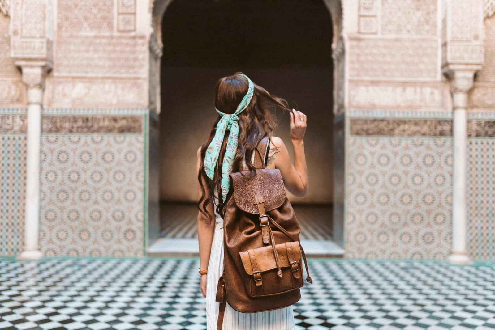 femme avec sac à dos marron debout près du bâtiment