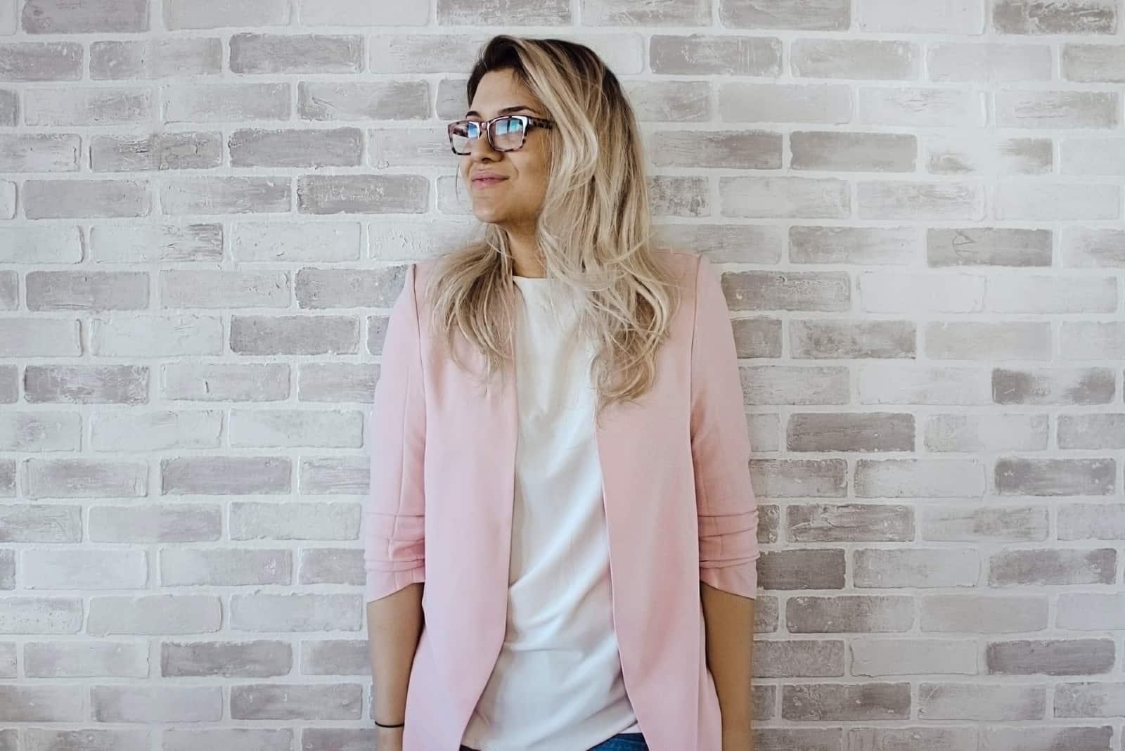 femme en blazer rose debout près du mur