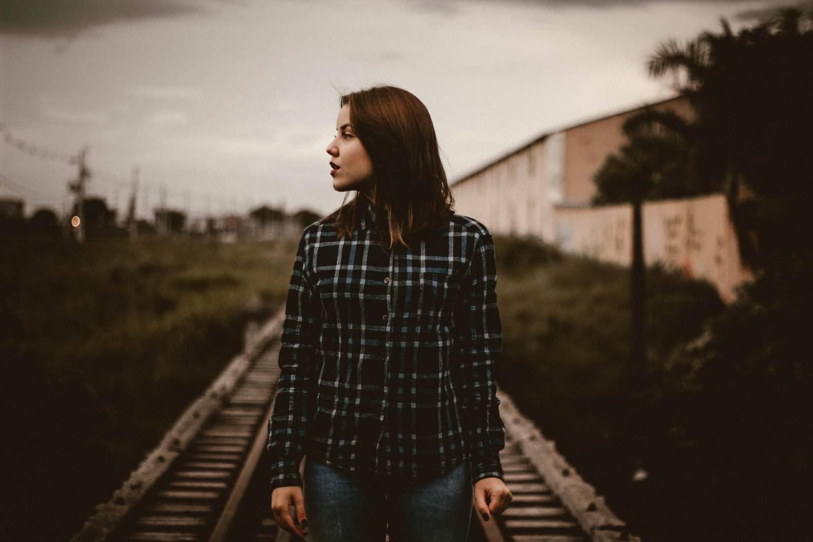 Femme en chemise à carreaux vert debout sur le rail du train