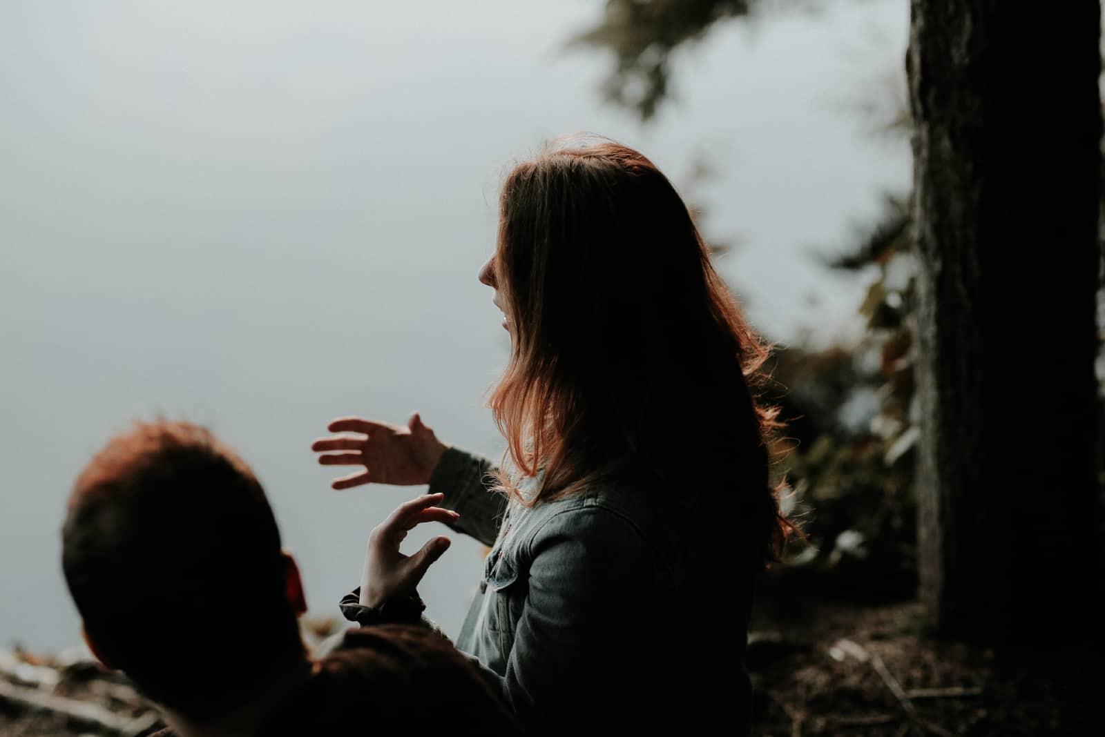 femme parlant à un homme assis près de l'eau