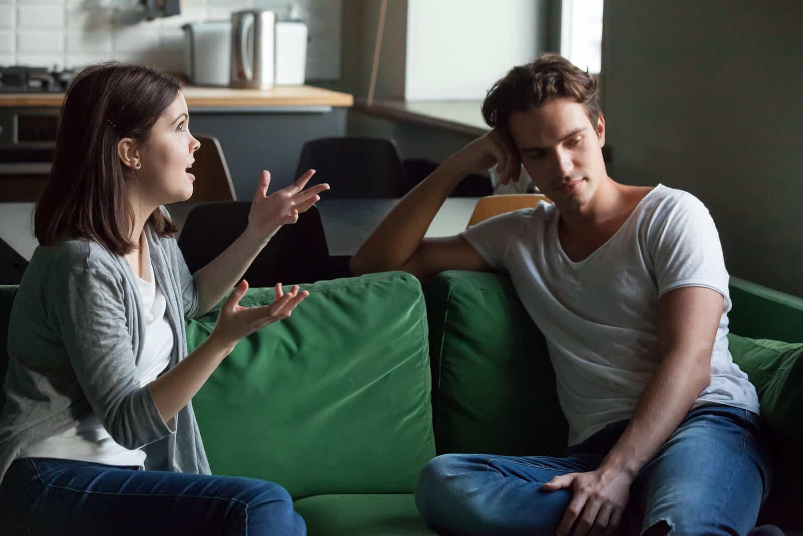 femme parlant à un homme assis sur un canapé