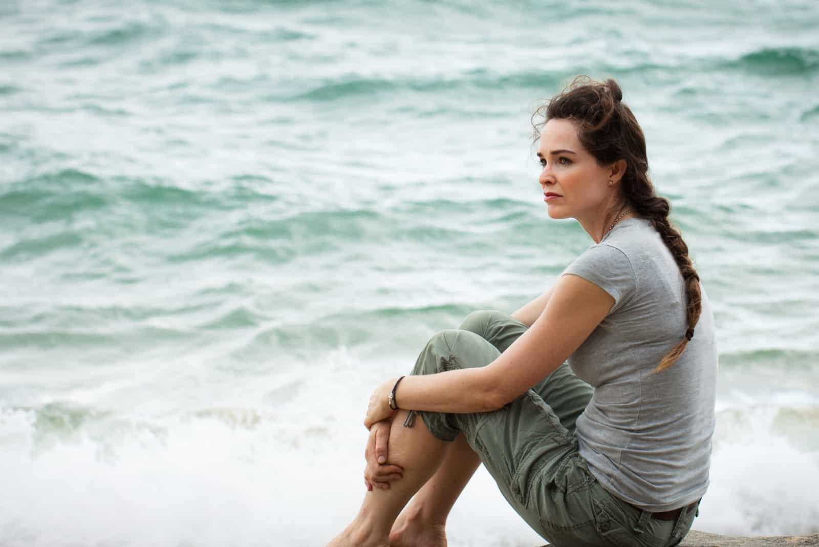 femme pensive assise au bord de l'océan