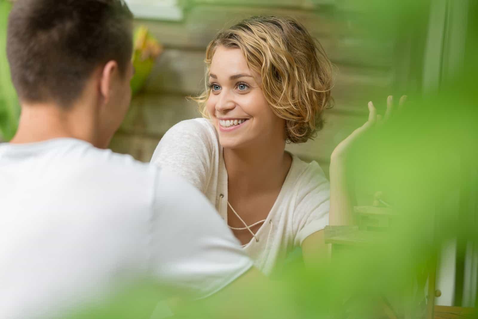 femme heureuse en haut blanc parler à l'homme