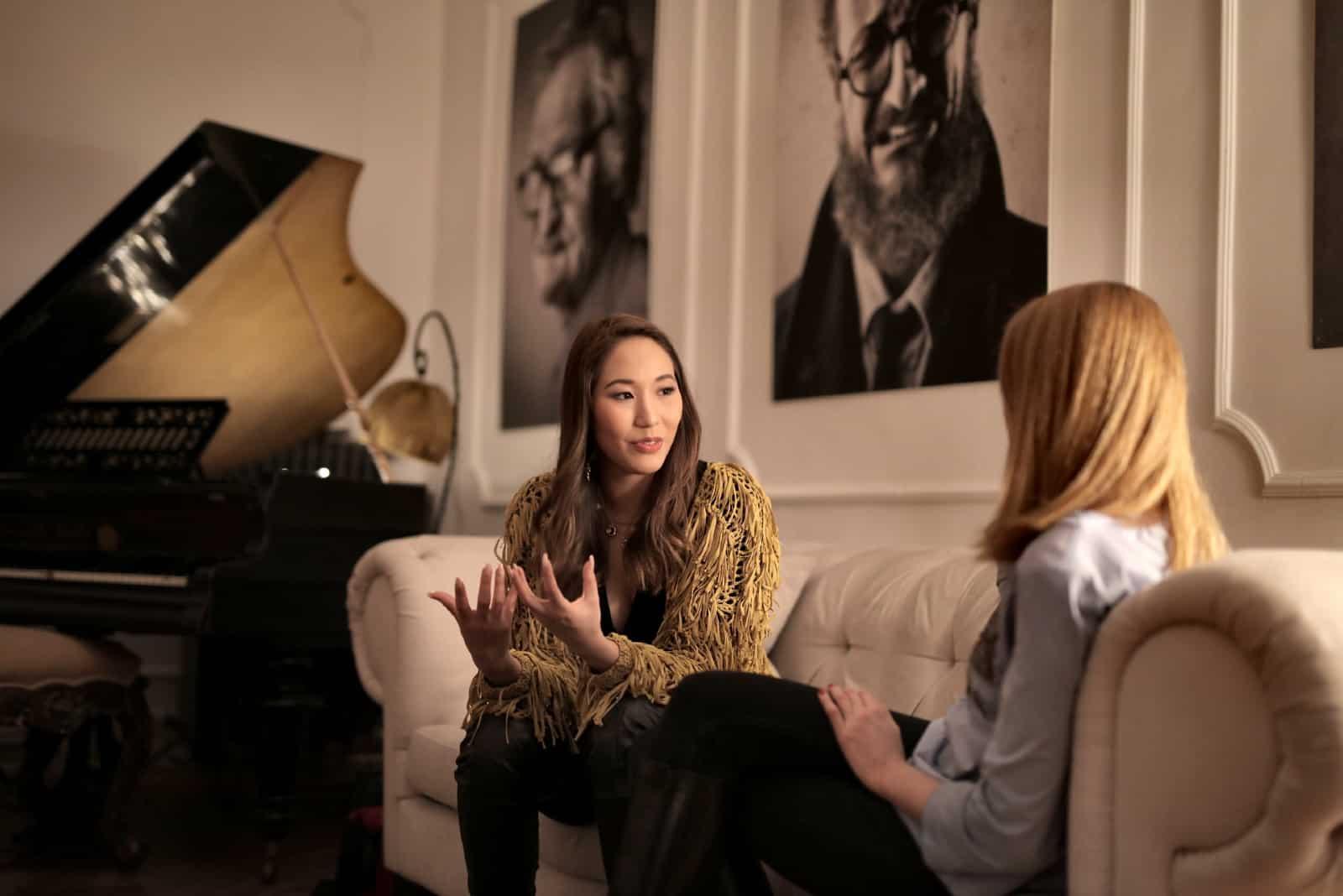 femme parlant à la femme assise sur le canapé