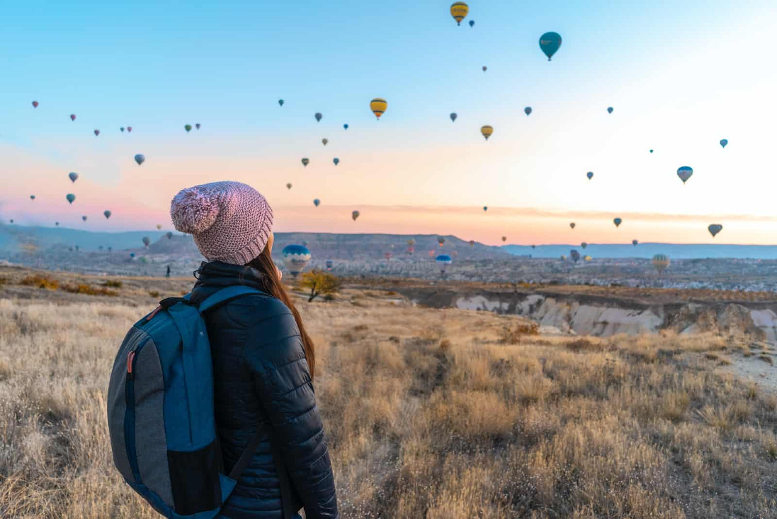 femme avec un sac à dos regardant des ballons à air chaud