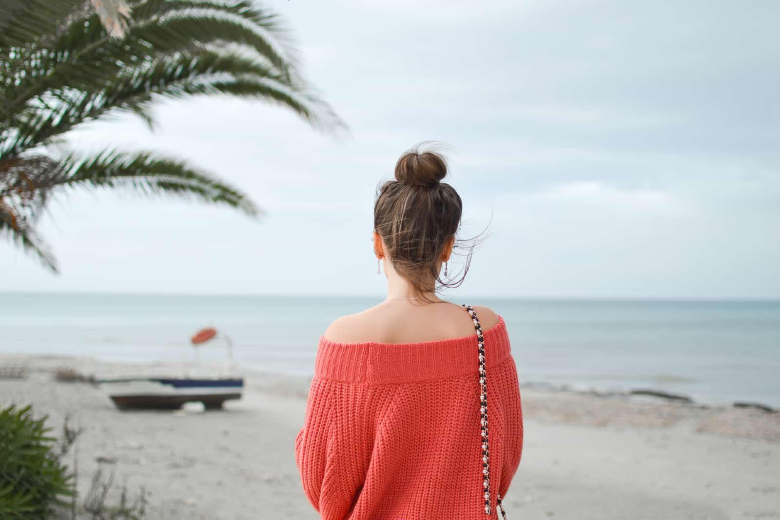 femme en pull rouge regardant la mer